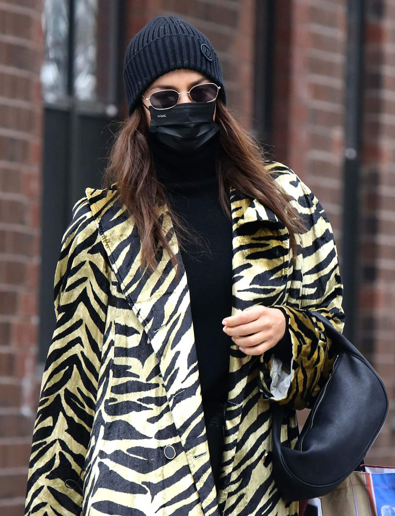 Irina Shayk accessorizes with Ruslan Baginskiy beanie, By Far bag, and Illesteva sunglasses