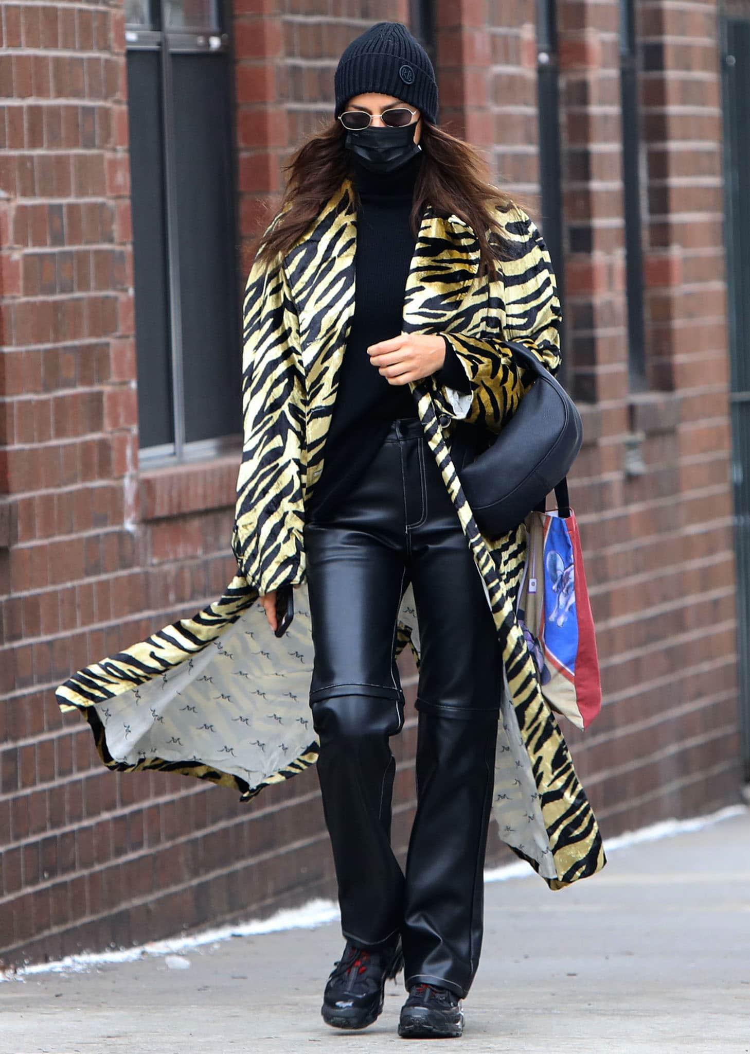 Irina Shayk wears a striking tiger-print coat with Niihai leather trousers