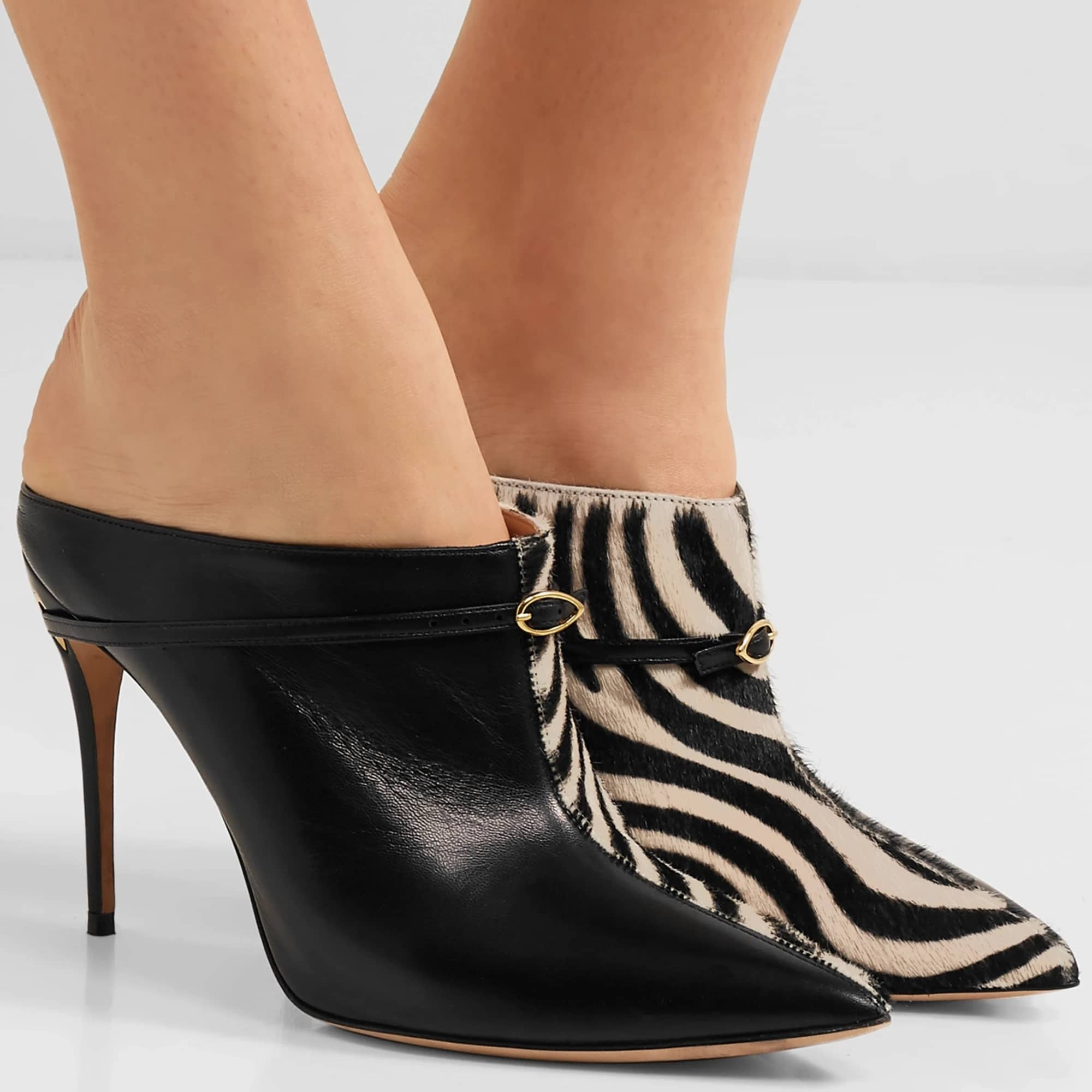 Made in Italy from zebra-print calf hair and smooth black leather, these mules are detailed with polished gold hardware