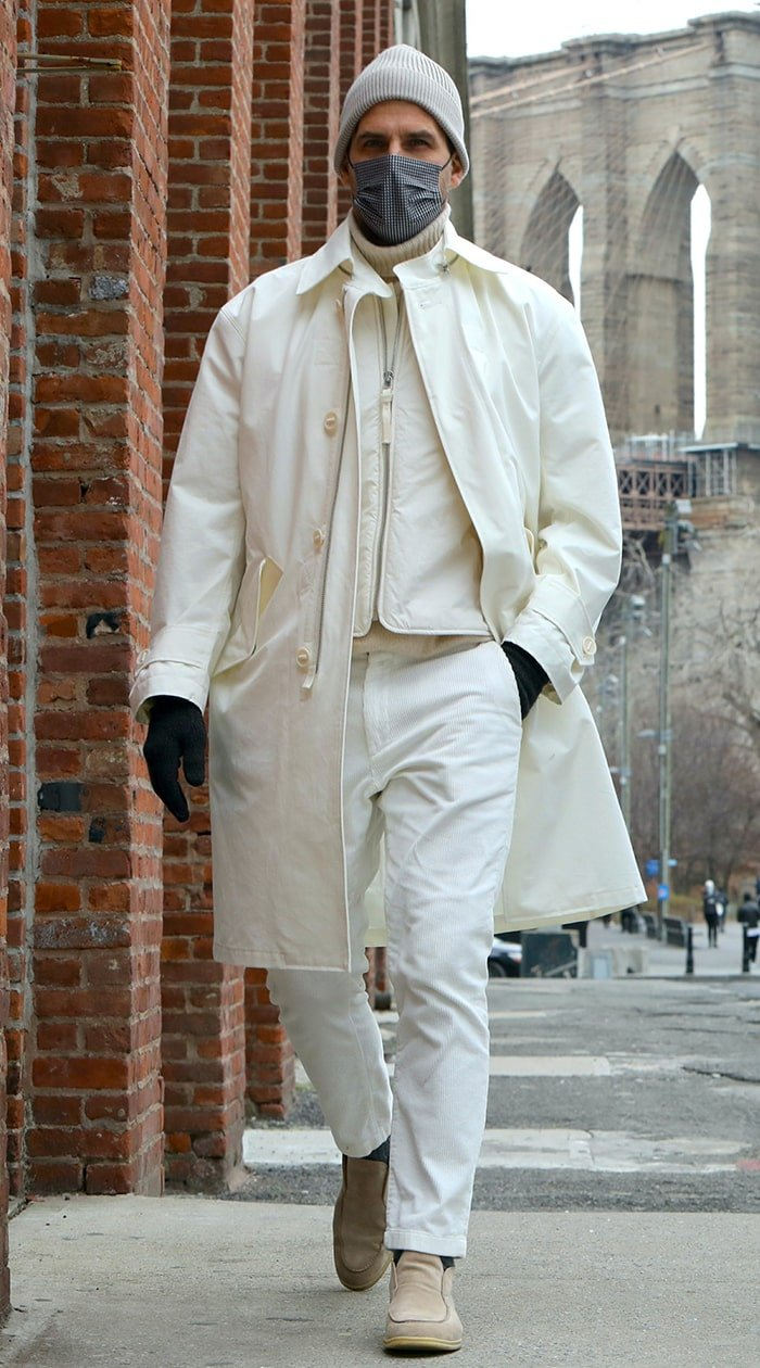 Johannes Huebl opts for an all-white winter outfit with a gray beanie and light brown shoes