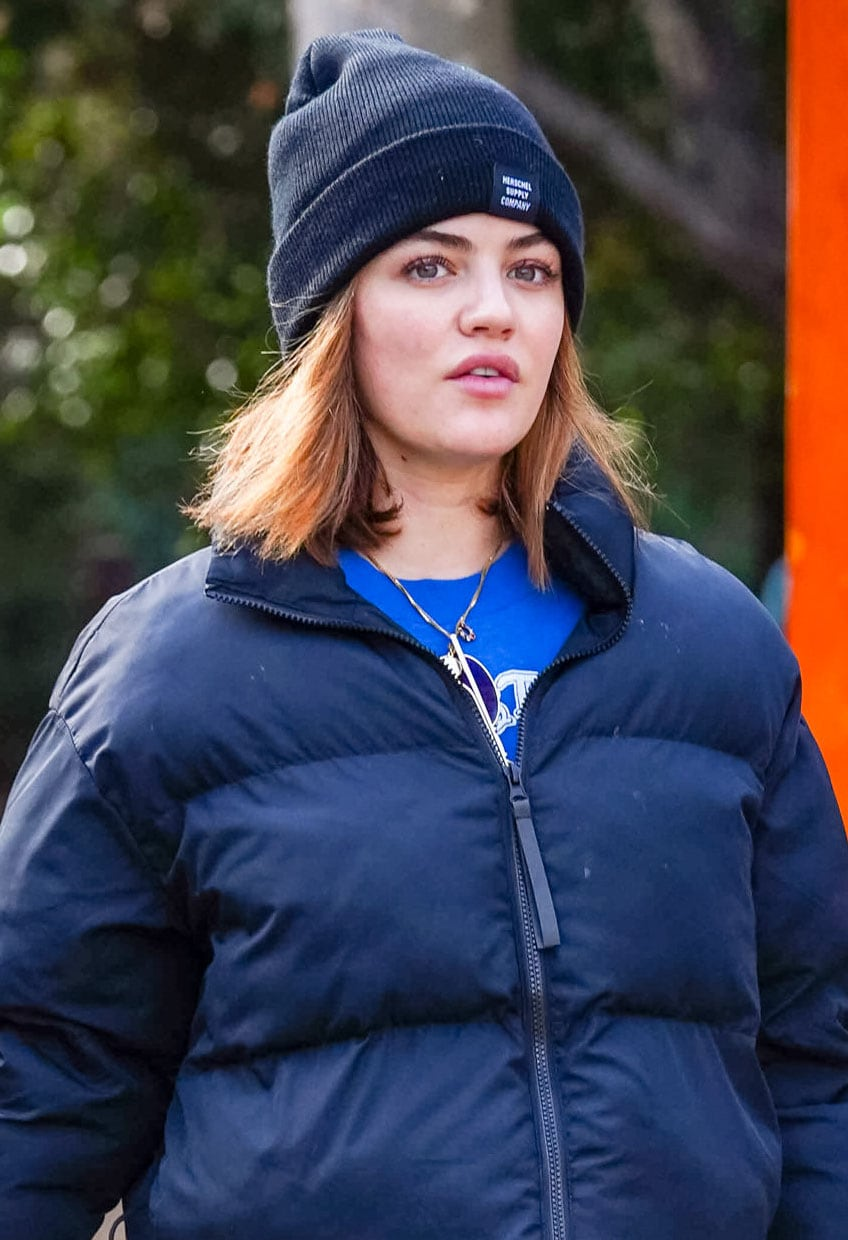 Lucy Hale wears a puff jacket with leggings and Herschel beanie