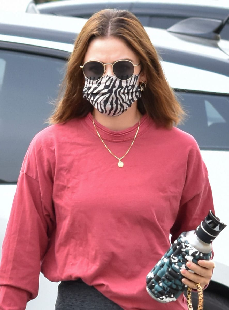 Lucy Hale keeps hair down and covers her face with Paradigm sunnies and Maskc face mask