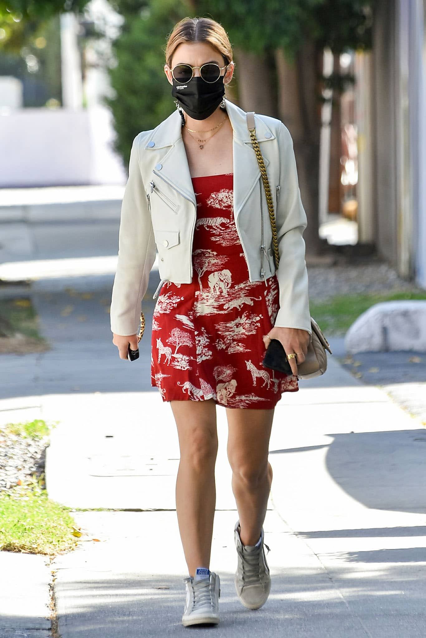 Lucy Hale looks stylish in a red Reformation mini dress and a white leather jacket