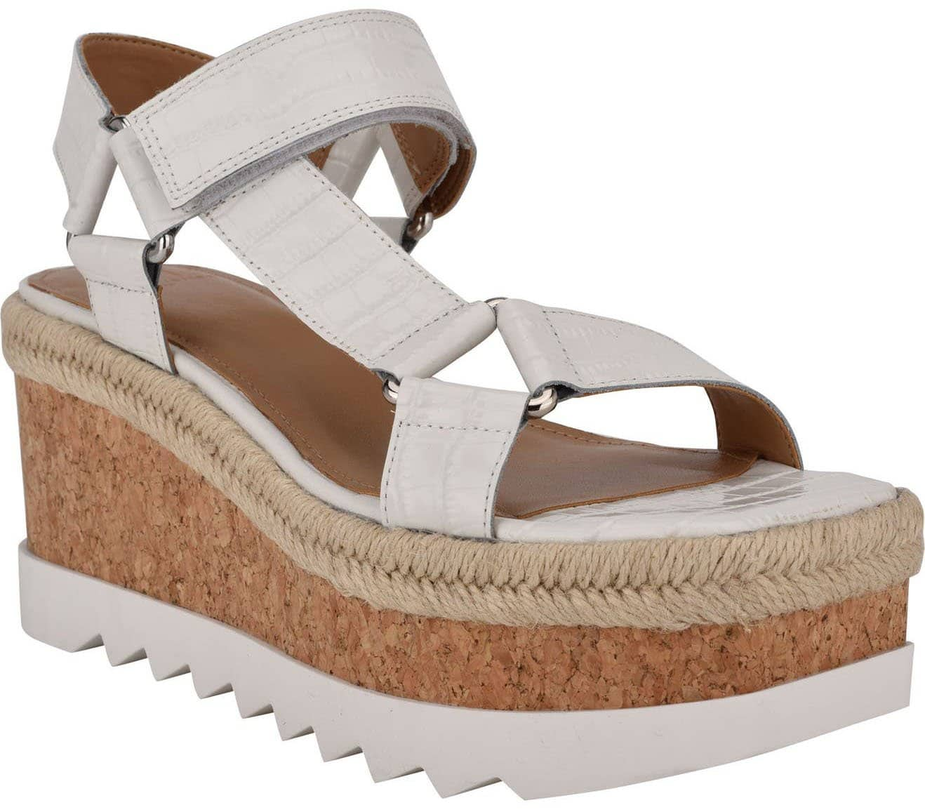 A sleek yet sporty sandal featuring trendy platform cork wedge with an espadrille-inspired trim