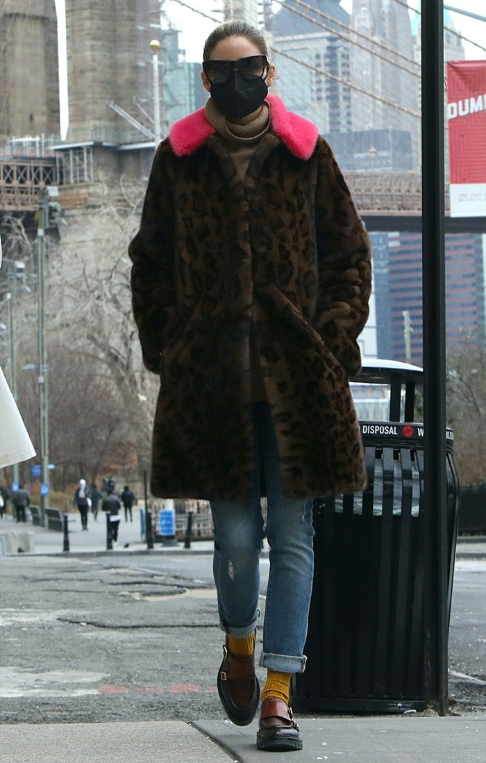 Olivia Palermo wears a leopard coat with a pink fur trim over a brown sweater and a pair of jeans