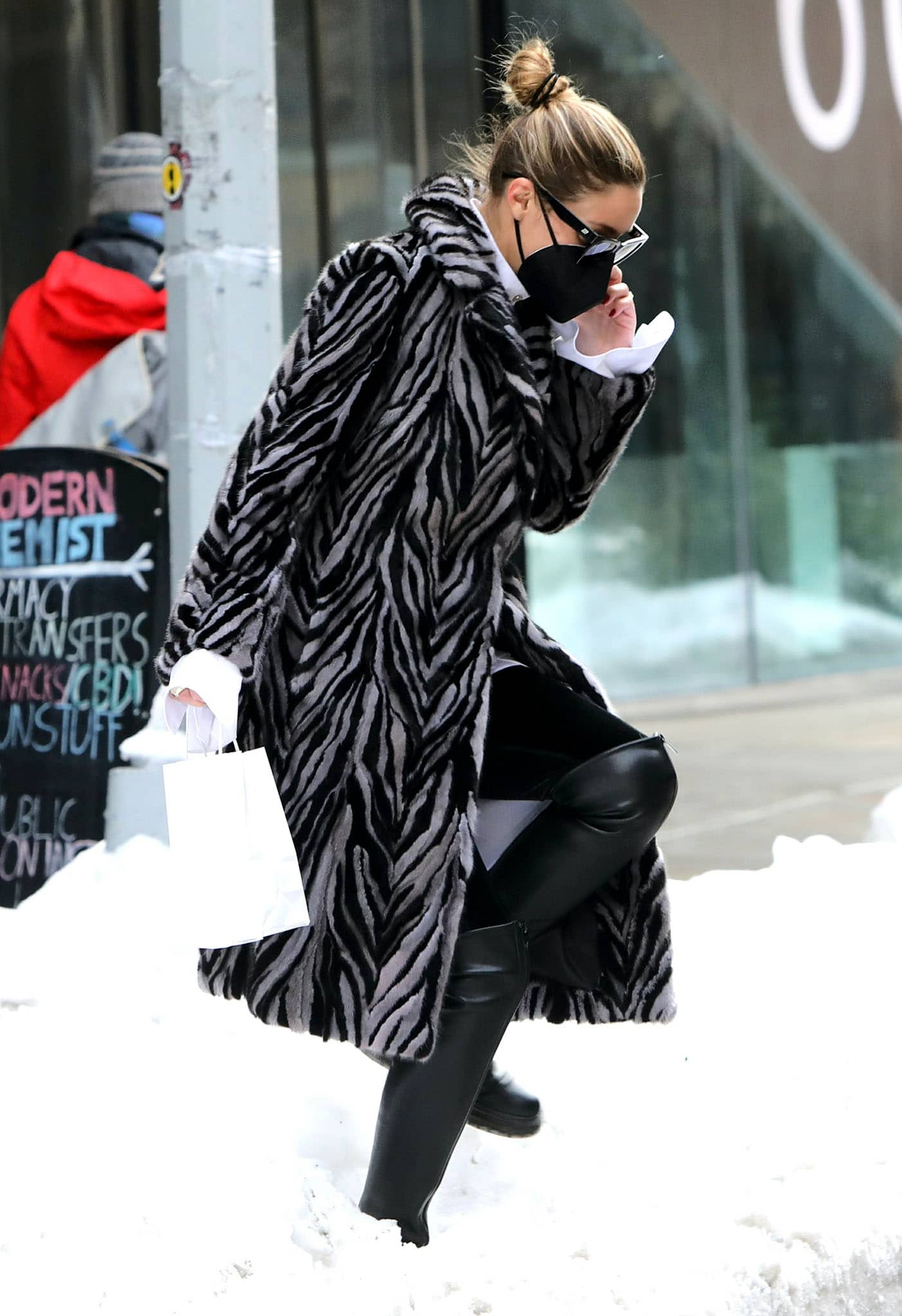 Olivia Palermo walks over a snow pile in Gianvito Rossi over-the-knee leather boots