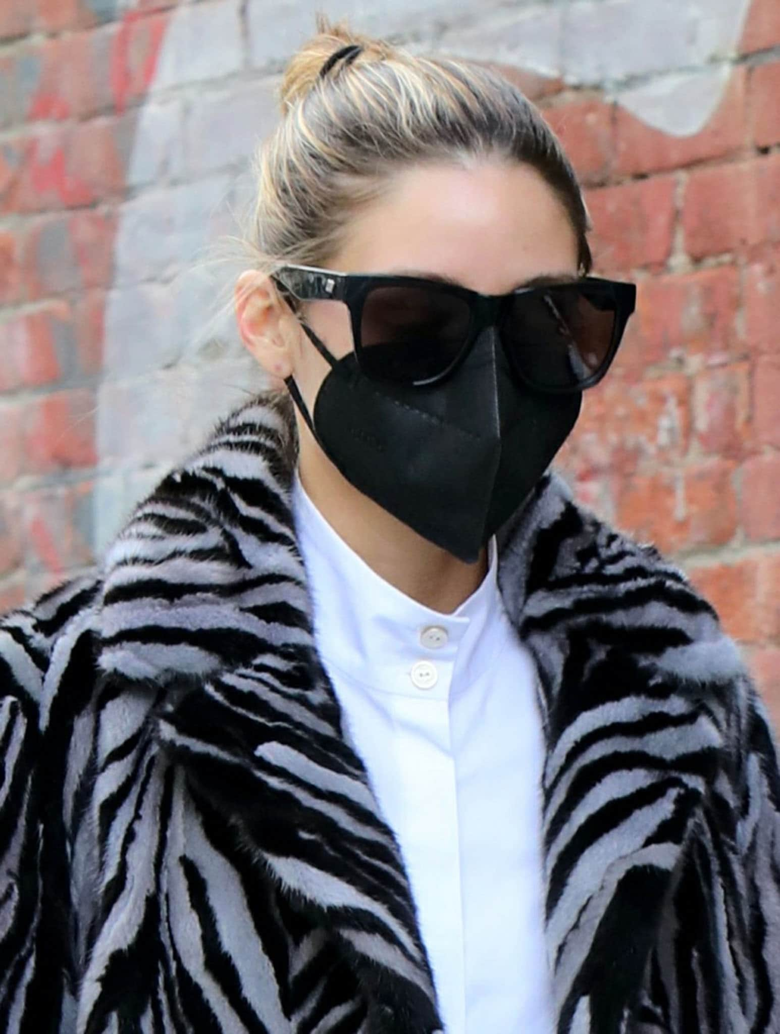 Olivia Palermo keeps things low-key with a casual bun, oversized sunglasses, and a black face mask