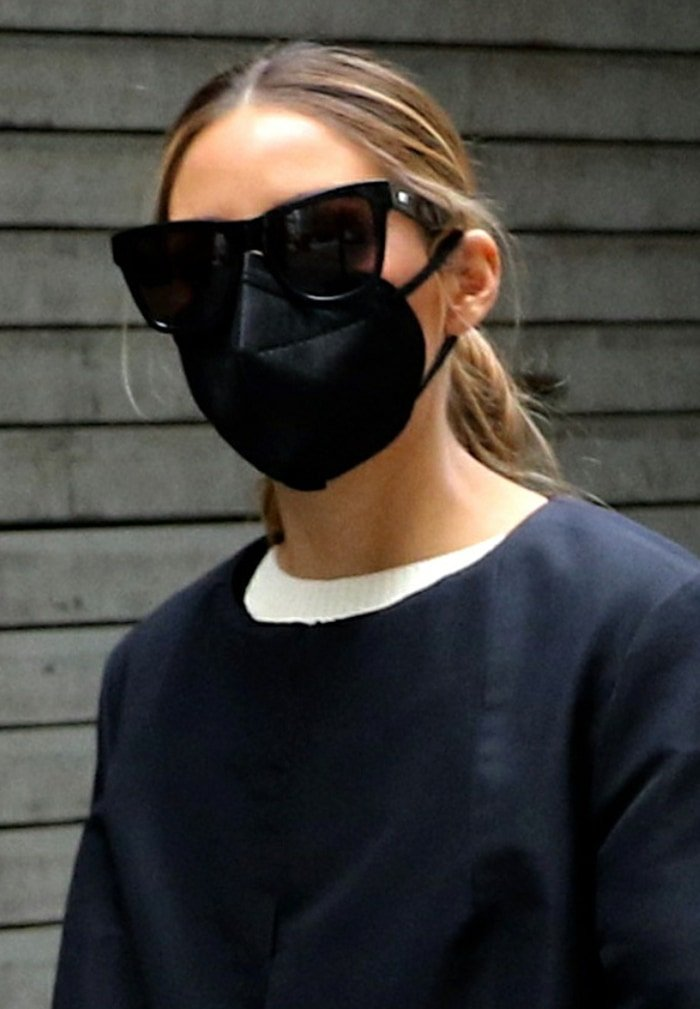 Olivia Palermo ties her hair back and stays safe with a black face mask