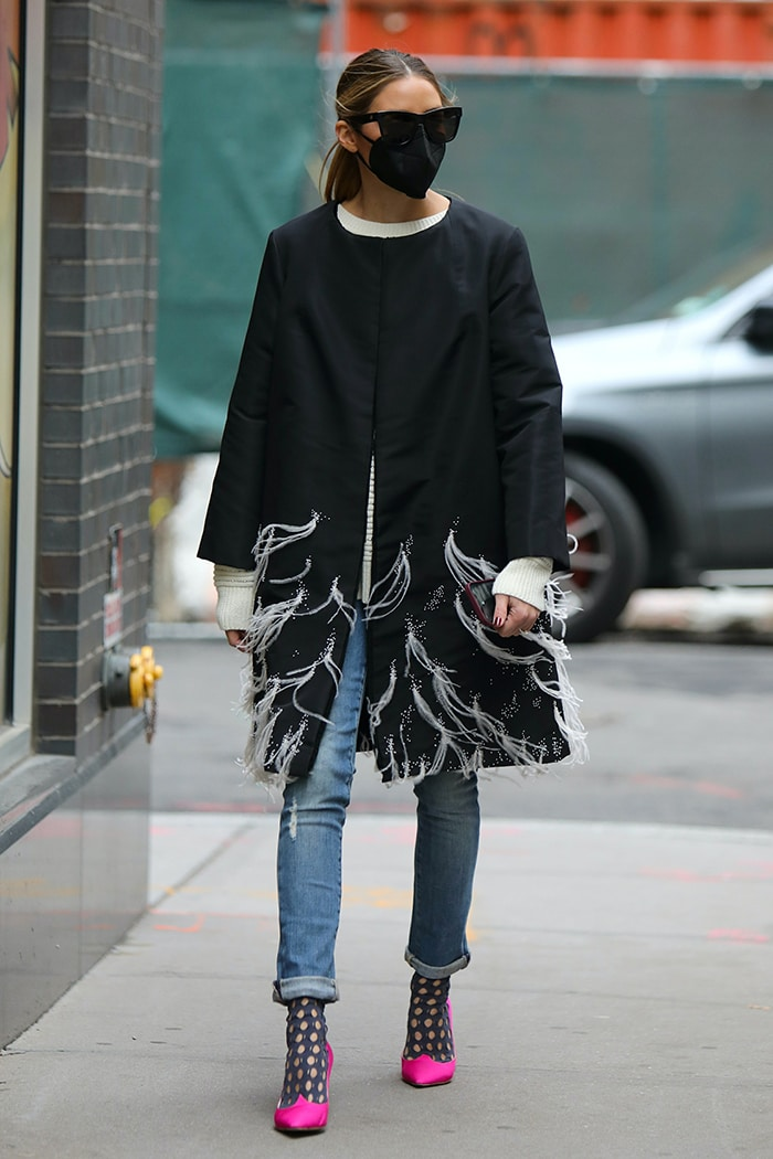 Olivia Palermo layers a feathered coat dress over a sweater and a pair of jeans