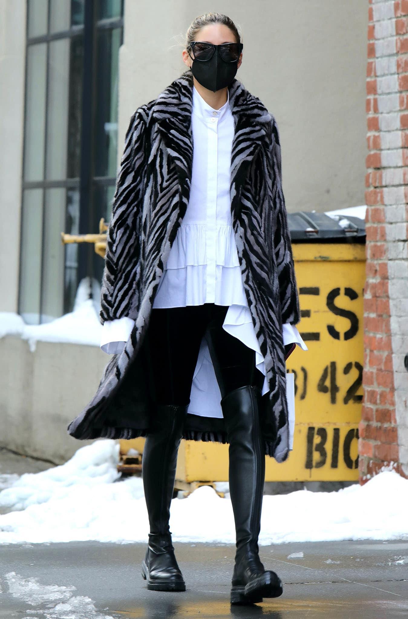 Olivia Palermo stays cozy in a Pologeorgis zebra-striped mink fur coat, white ruffled top, and leggings
