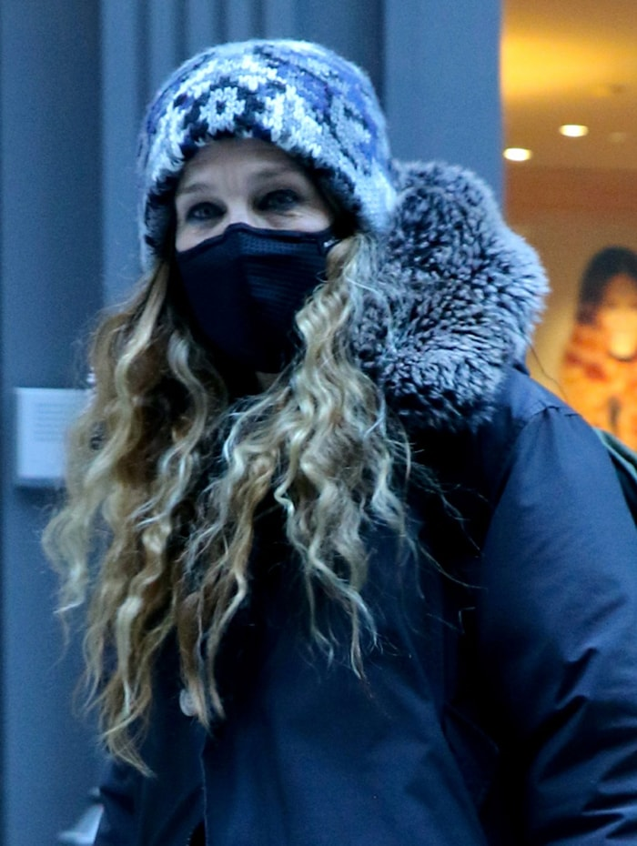 Sarah Jessica Parker bundles up in a black fur-trimmed coat and a patterned knit beanie