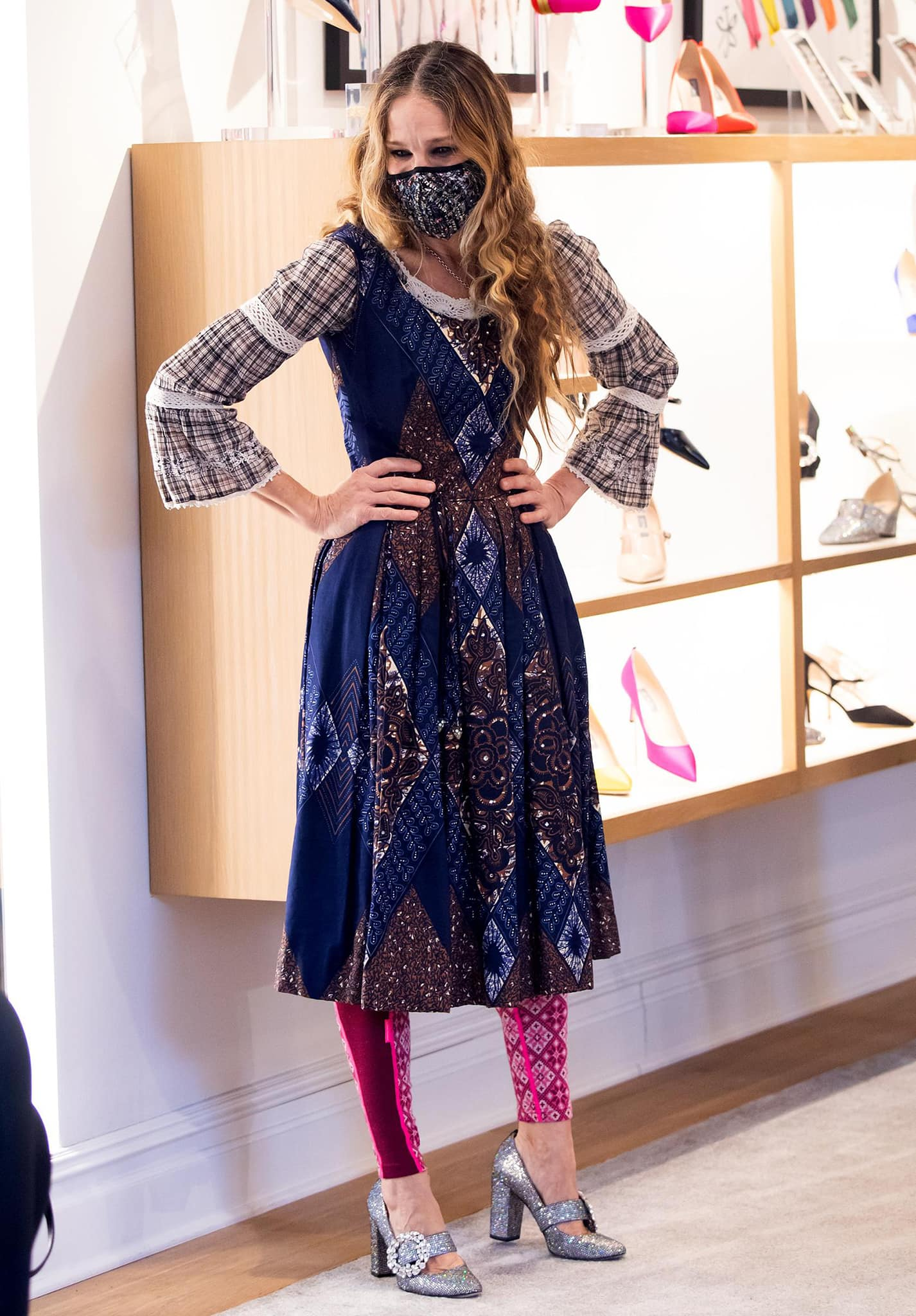 Underneath her coat, Sarah Jessica Parker wears a sleeveless paisley-printed dress with a prairie blouse and pink leggings