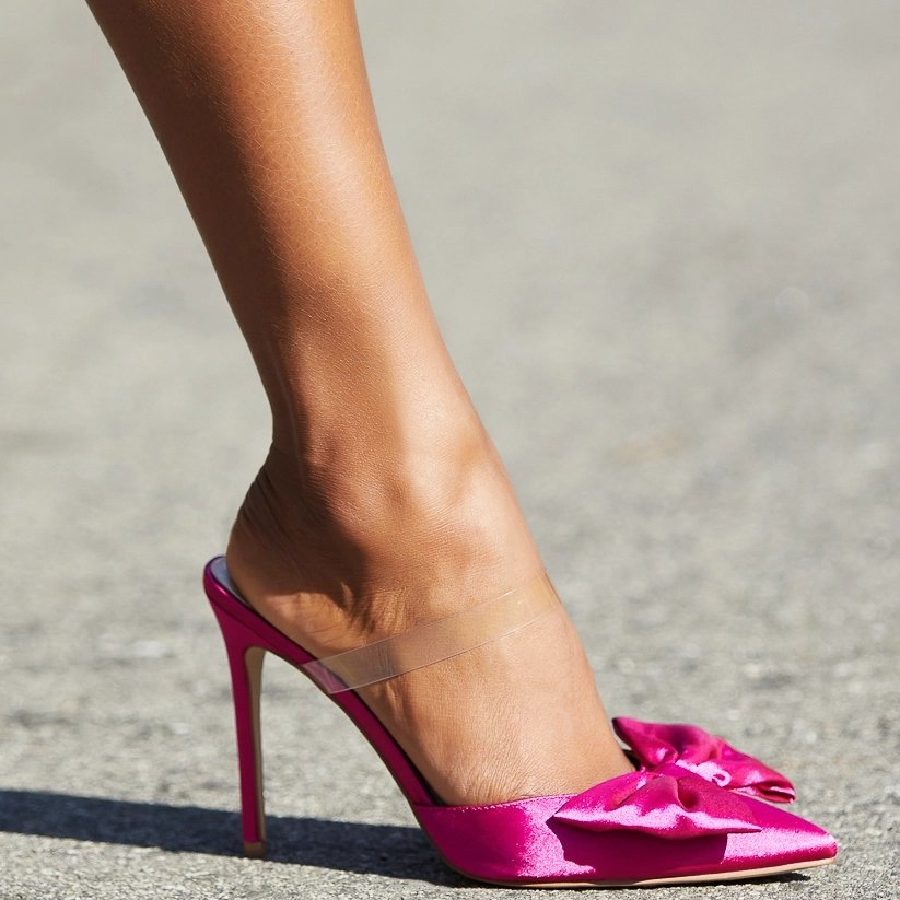 A pink slip-on pump featuring a stiletto heel, clear strap, and bow detail