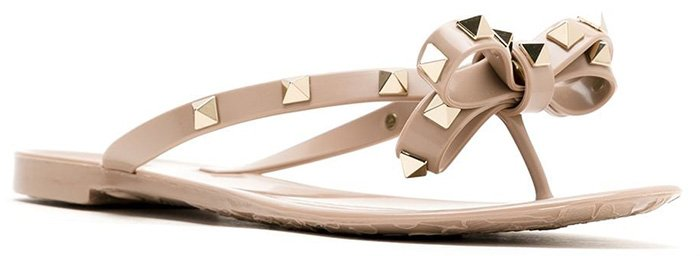 These Rockstud bow sandals from Valentino Garavani feature a bow detail, gold-tone Rockstud embellishments, a branded insole, a flat rubber sole, and a thong strap