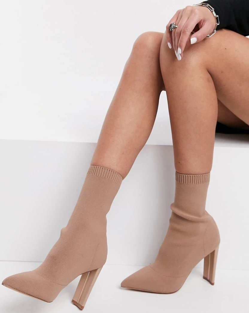 A sock-like upper with a ribbed collar made from recycled materials creates stylish comfort in this pointy-toe bootie set on a lofty heel