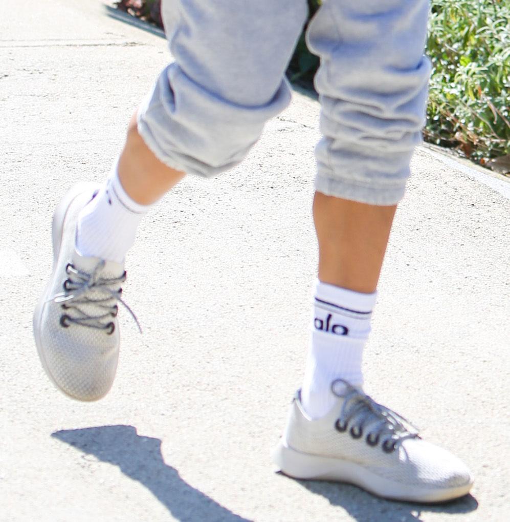 Alessandra Ambrosio wears Alo Yoga Throwback socks with Allbirds Tree Dashers sneakers