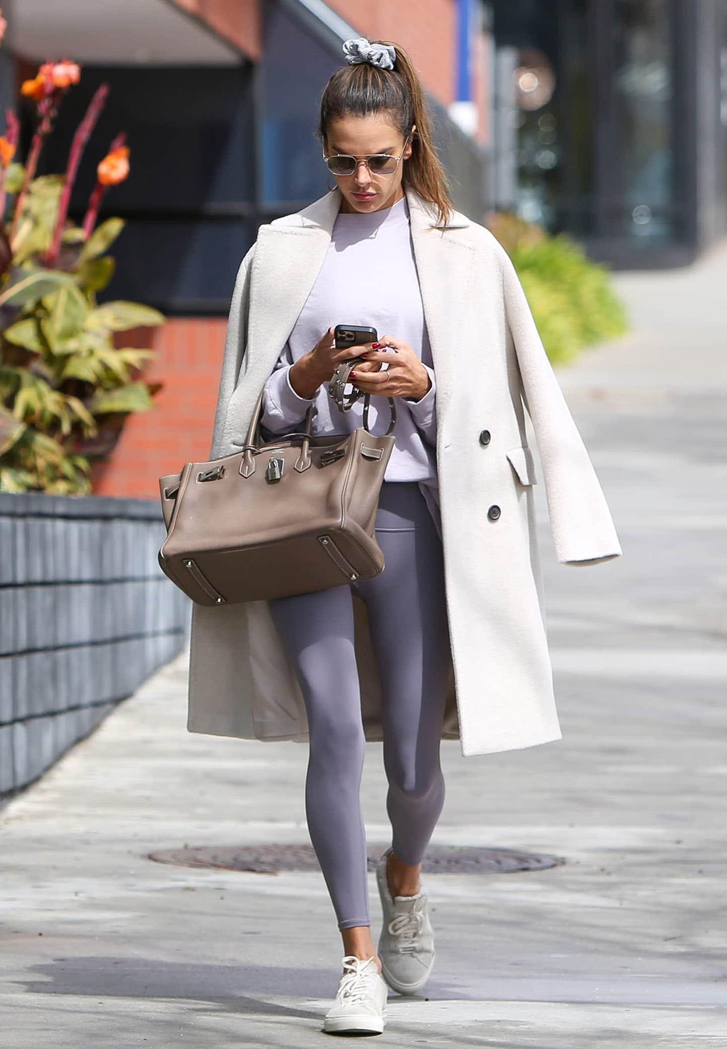 Alessandra Ambrosio wears Alo Yoga purple leggings and matching sweatshirt with a white coat