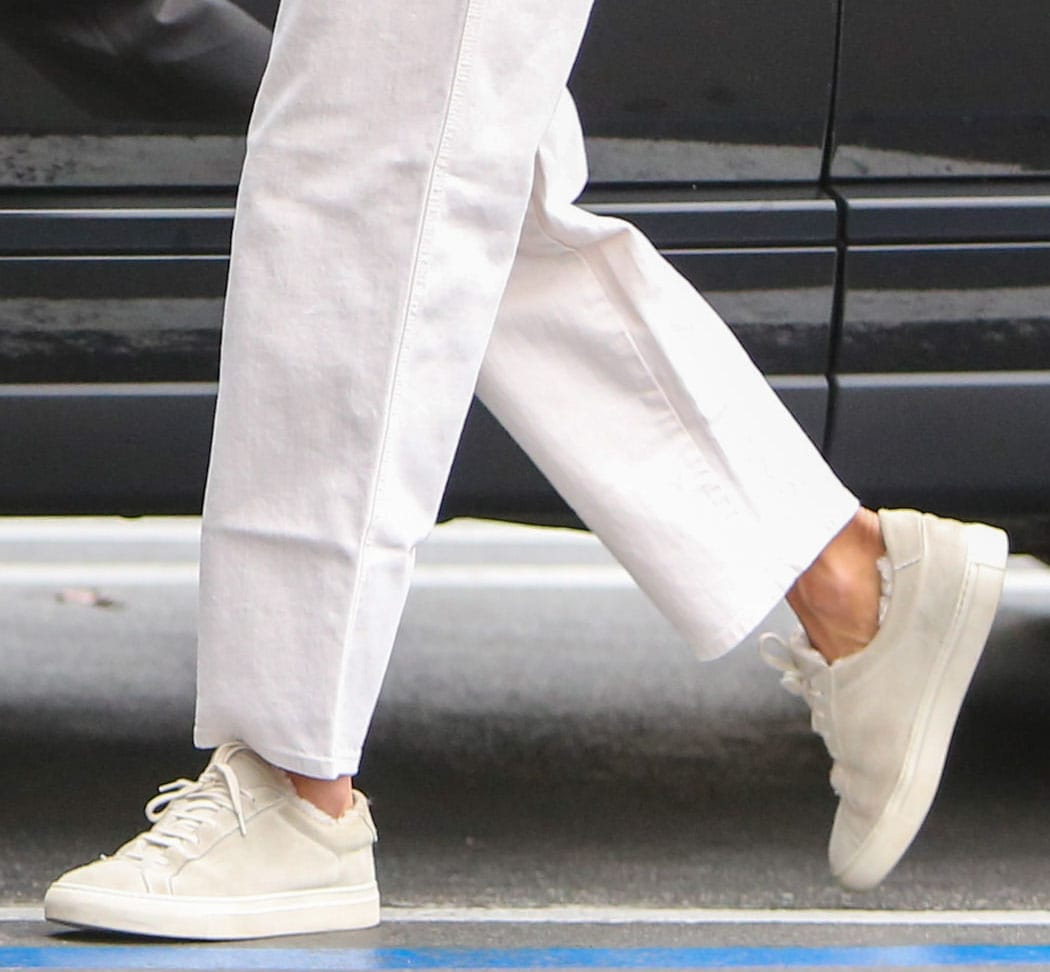 Alessandra Ambrosio teams her Mother striped sweater and straight-leg jeans with Common Projects sneakers