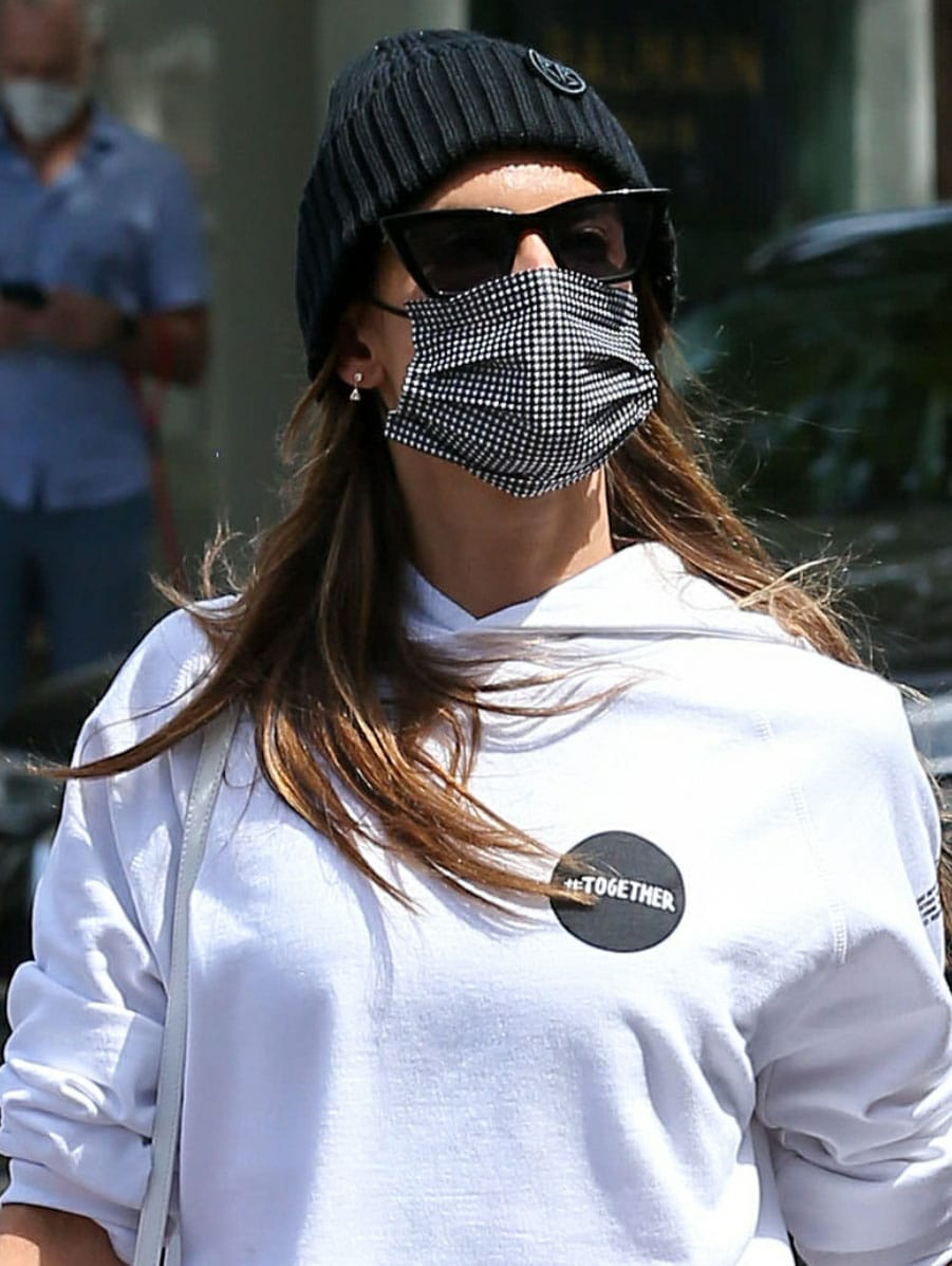 Alessandra Ambrosio styles her sporty look with a Ruslan Baginskiy beanie, a plaid face mask, and black cat eye sunglasses