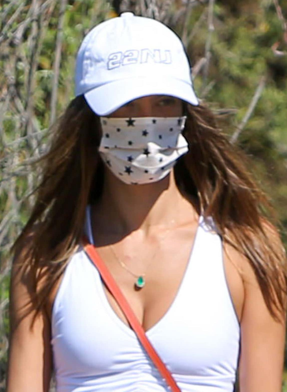 Alessandra Ambrosio keeps things low-key with a white cap and a star-patterned face mask