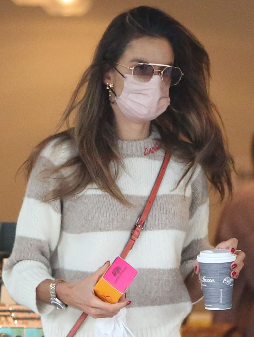 Alessandra Ambrosio wears her long wavy tresses down and styles her look with sunglasses, pink face mask, and gold earrings