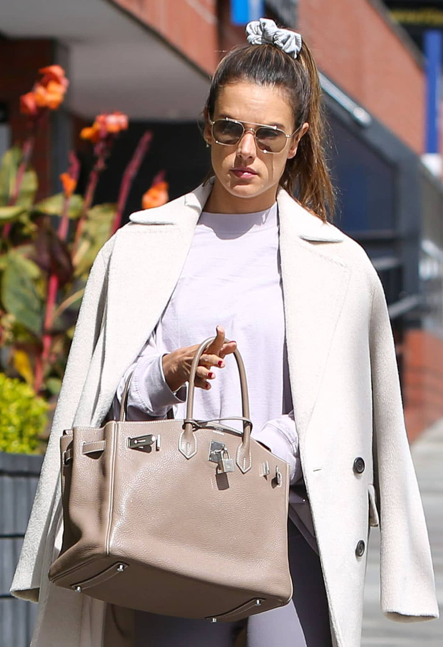 Alessandra Ambrosio wears a scrunchie and carries a Hermes Birkin bag in 35cm Etoupe