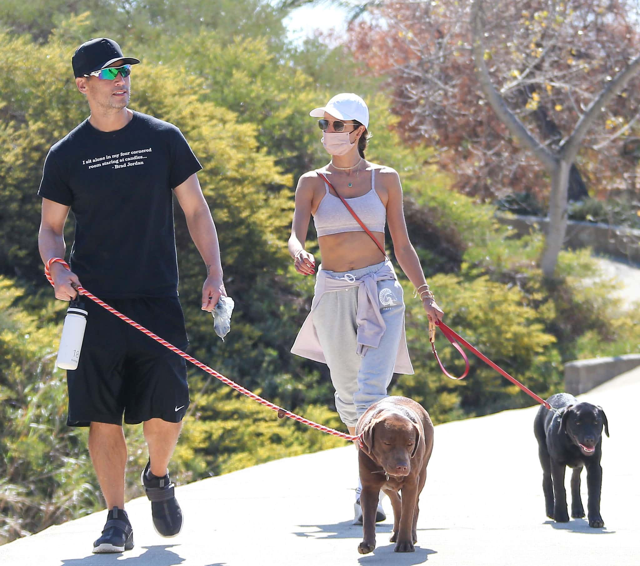Alessandra Ambrosio's male companion wears a black tee with black basketball shorts, cap, and sneakers