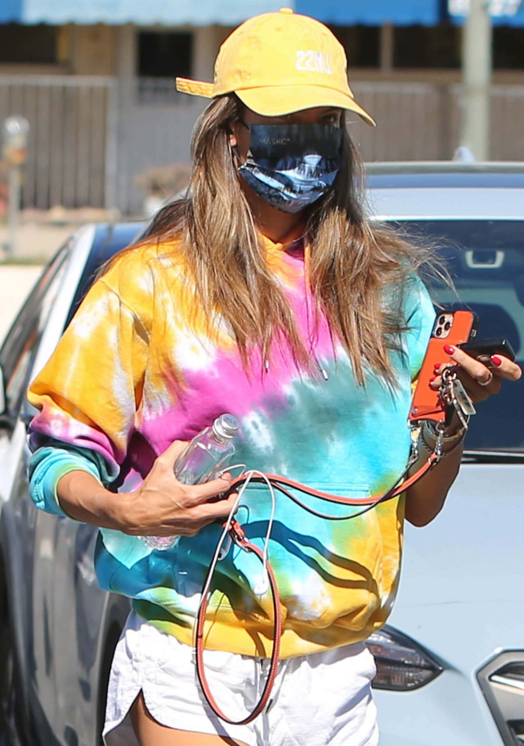 Alessandra Ambrosio styles her summery look with a cap, tie-dye face mask, and flip-flops