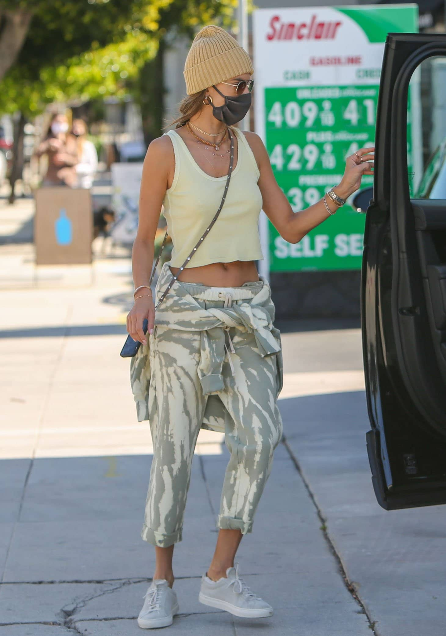 Alessandra Ambrosio flashes her abs in a yellow crop tank top and sage green tie-dye joggers