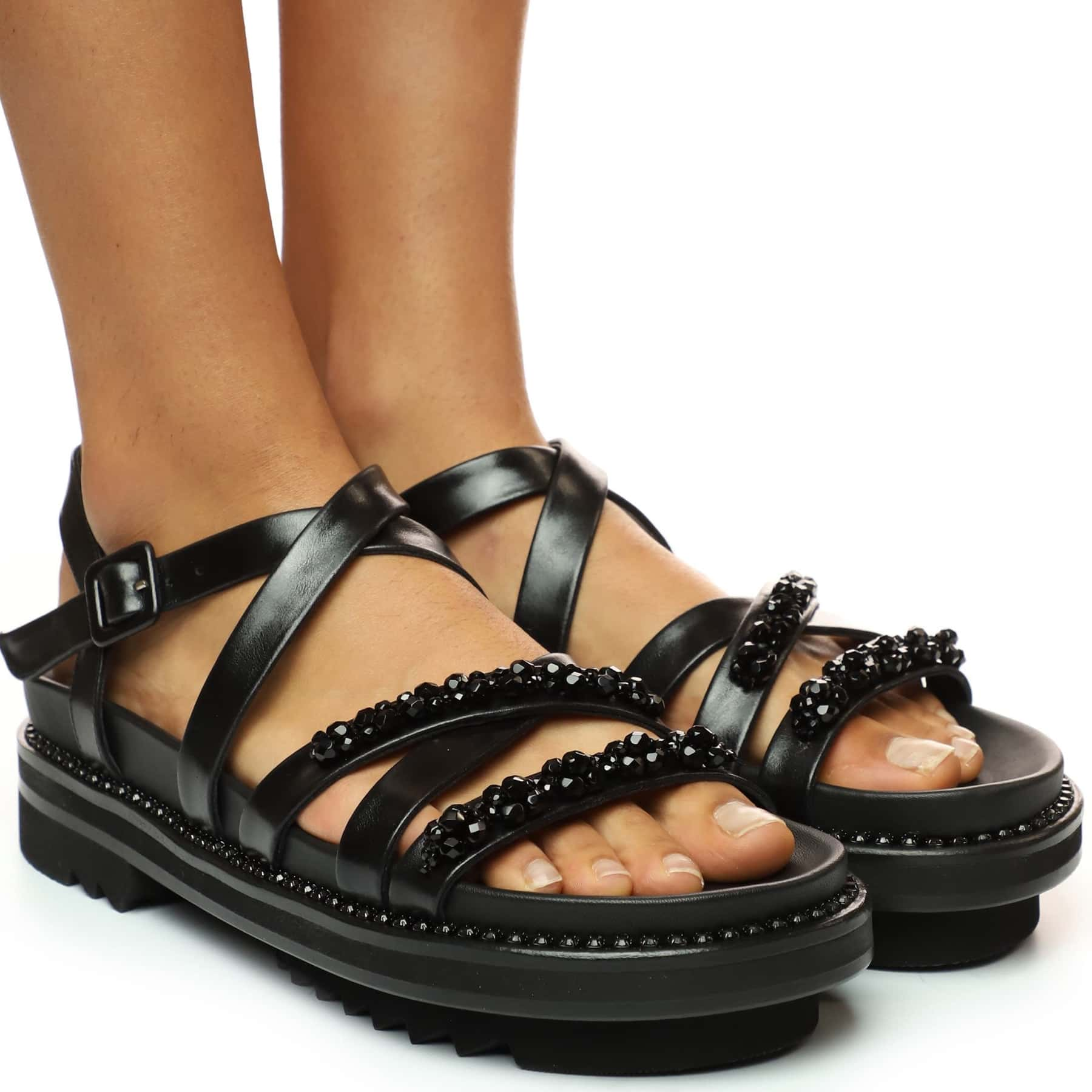 Faceted jet-black beads glam up this crisscross-strap, lug-platform sandal that's part sporty casual and part couture