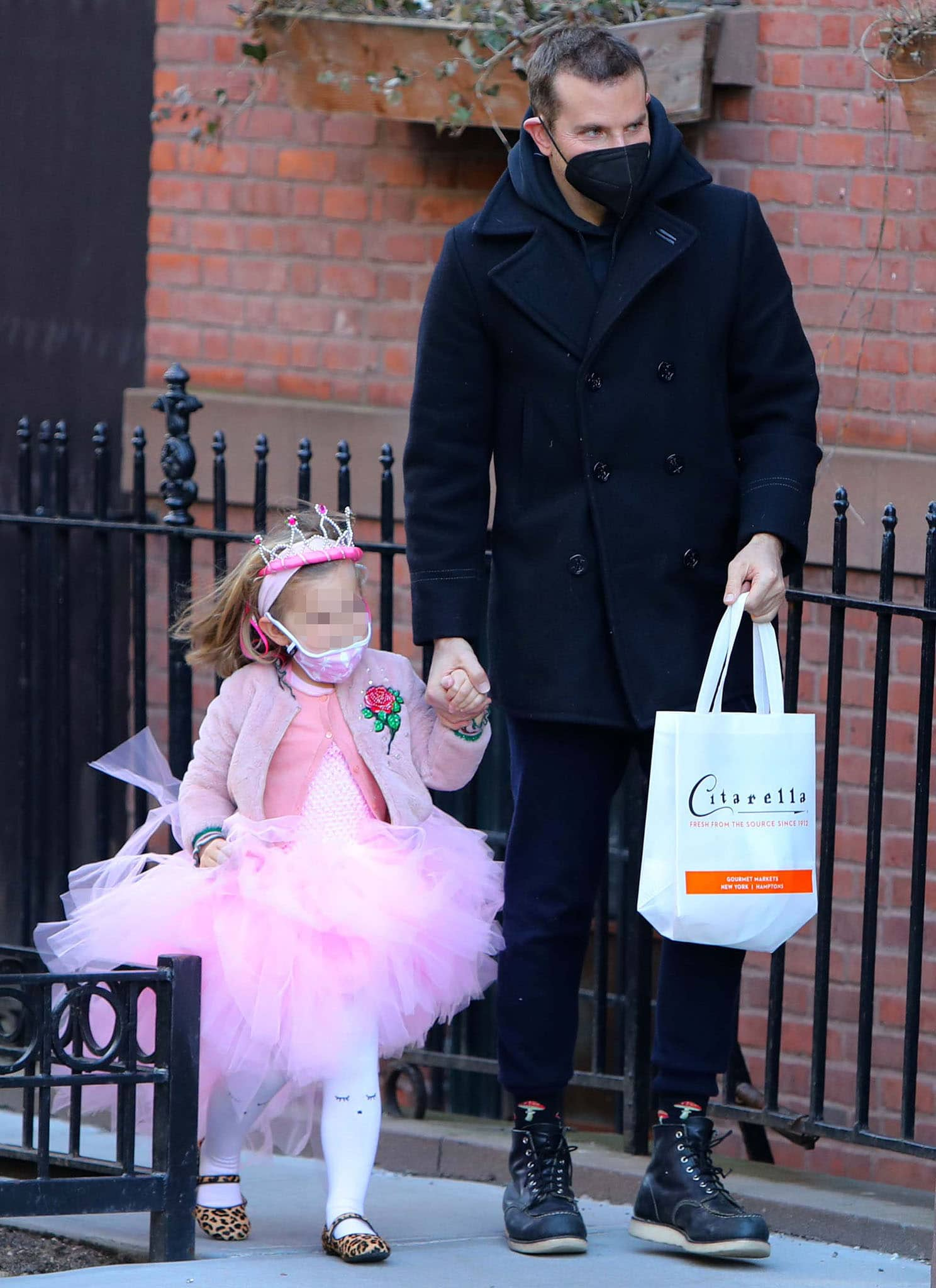 Bradley Cooper wears a black pea coat as he holds hands with his daughter