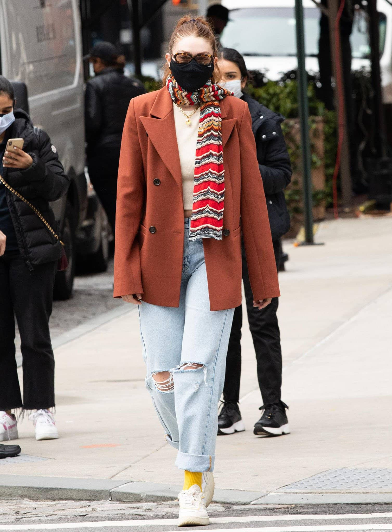Gigi Hadid adds more color to her chic look with a striped scarf and a pair of Petals and Peacocks yellow socks