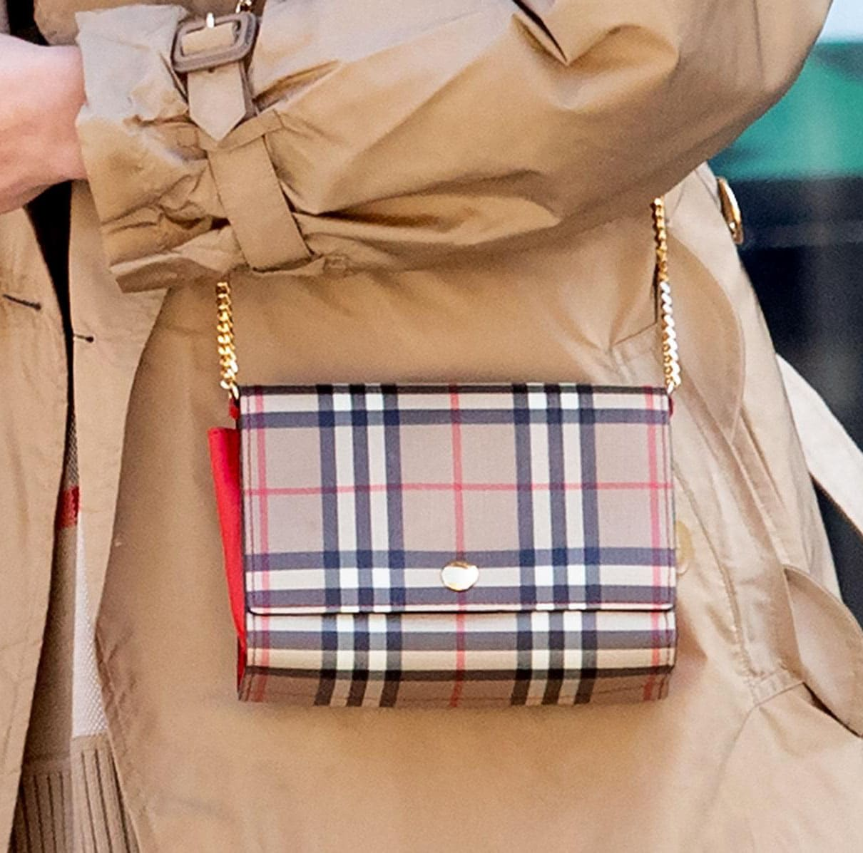 Irina Shayk carries a Burberry check leather wallet over her shoulder