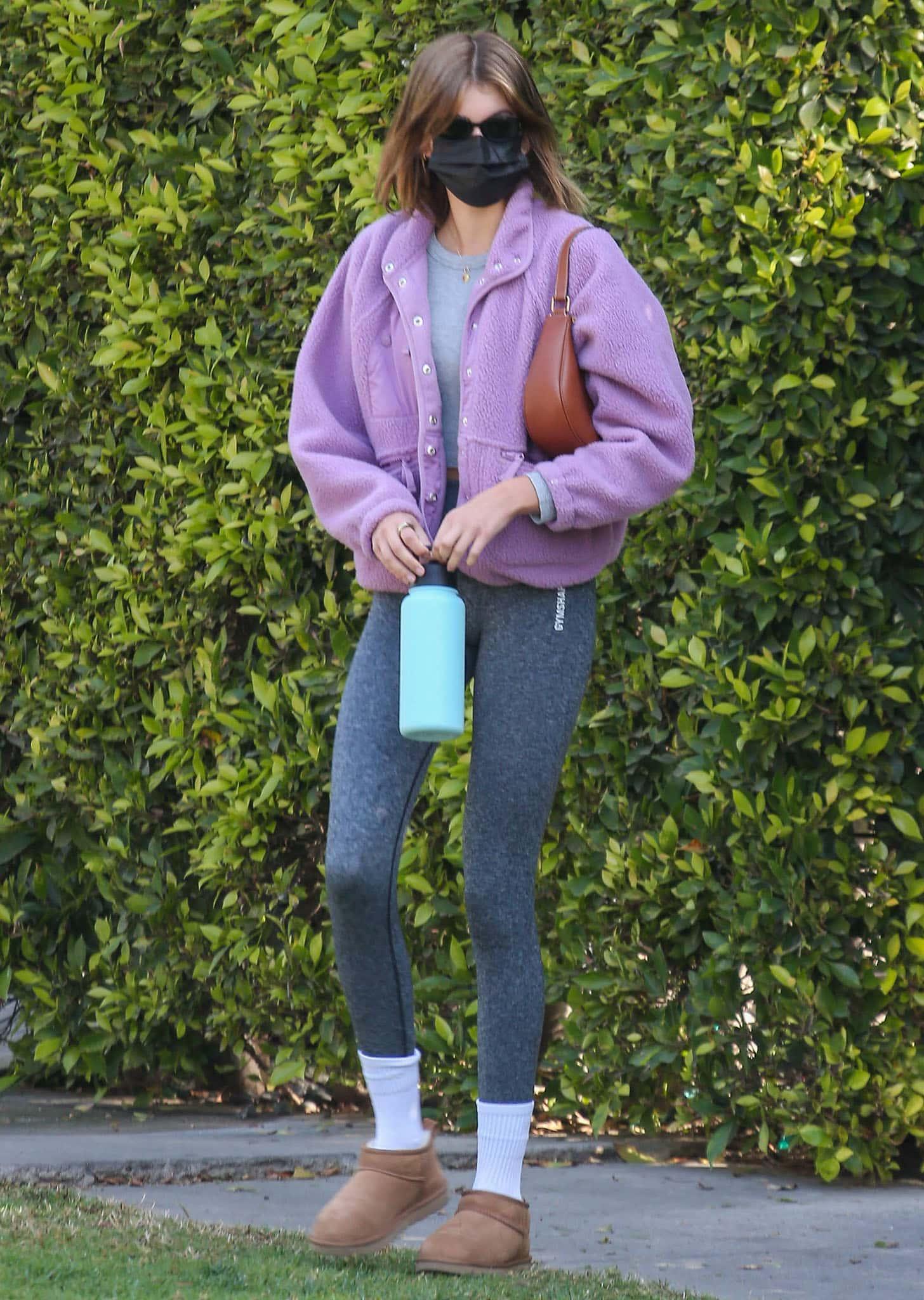 Kaia Gerber flaunts her long slender legs in Gymshark leggings and Free People pink fleece jacket