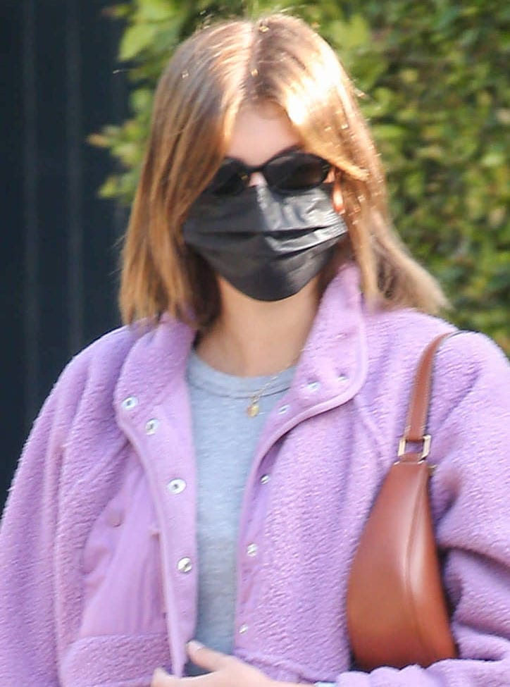 Kaia Gerber covers her face with a black face mask and a pair of Kate Young for Tura sunnies