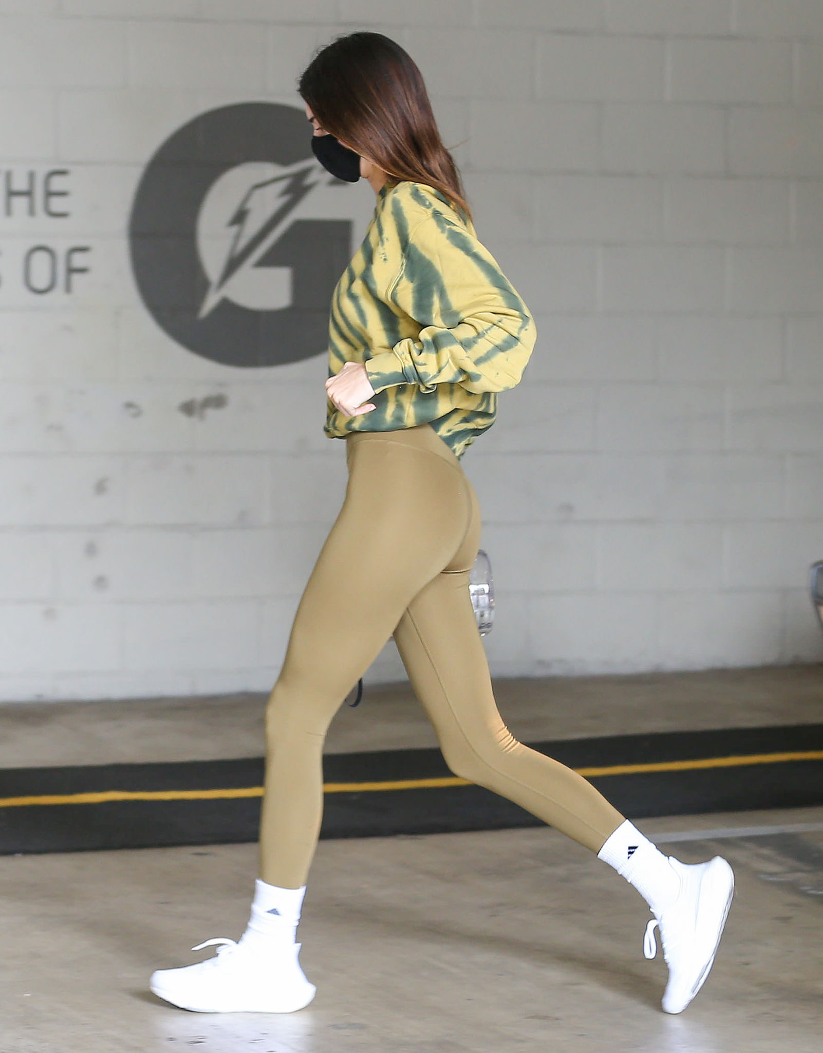 Kendall Jenner wears olive green Alo leggings and a Good American tie-dye sweatshirt to the gym
