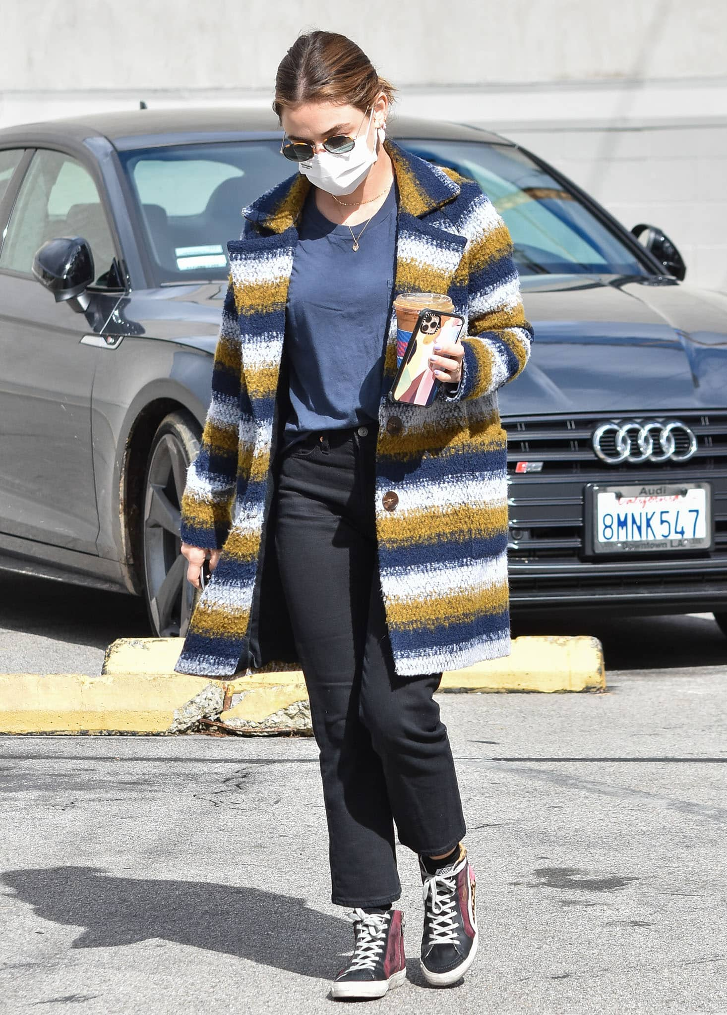 Lucy Hale wears a chic multicolored striped coat with a navy tee and black jeans