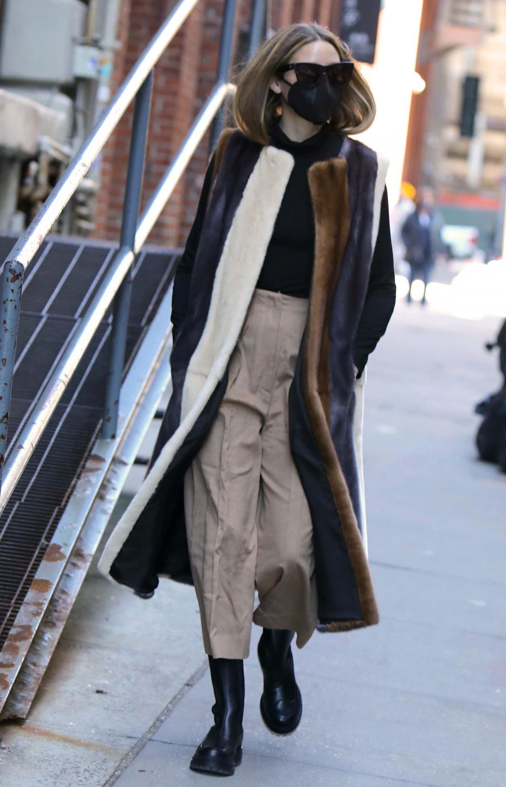 Olivia Palermo in a winter chic Pologeorgis faux fur striped vest, black turtleneck sweater, and khaki pants