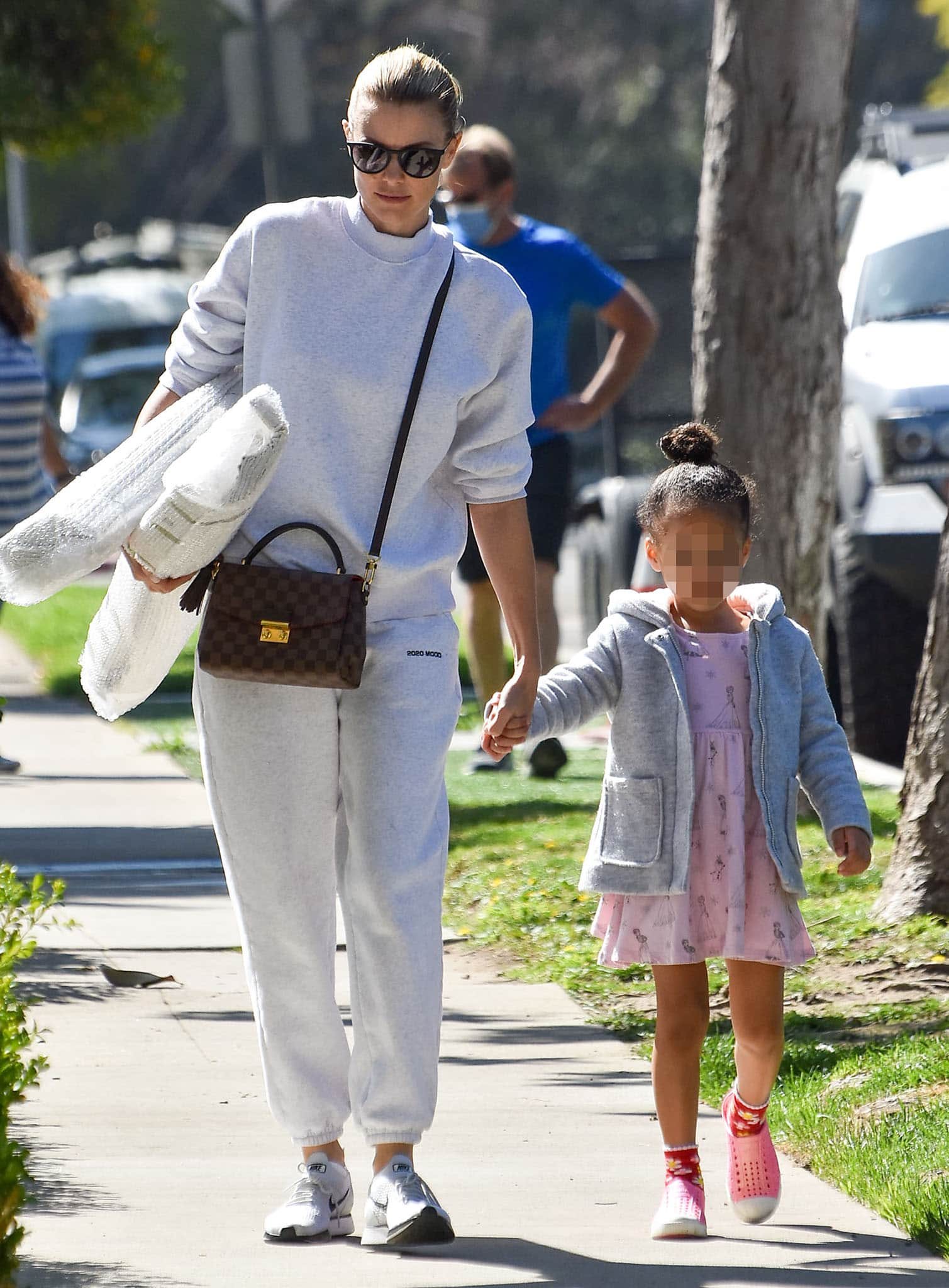 Paige Butcher wearing a gray sweater, sweatpants, and Nike shoes while out with daughter Izzy in Los Angeles on March 6, 2021