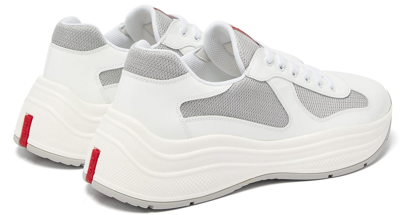 The Prada America's Cup feature white patent and gray mesh upper with the house's hallmark Linea Rossa logo in red rubber at the tongue and rear