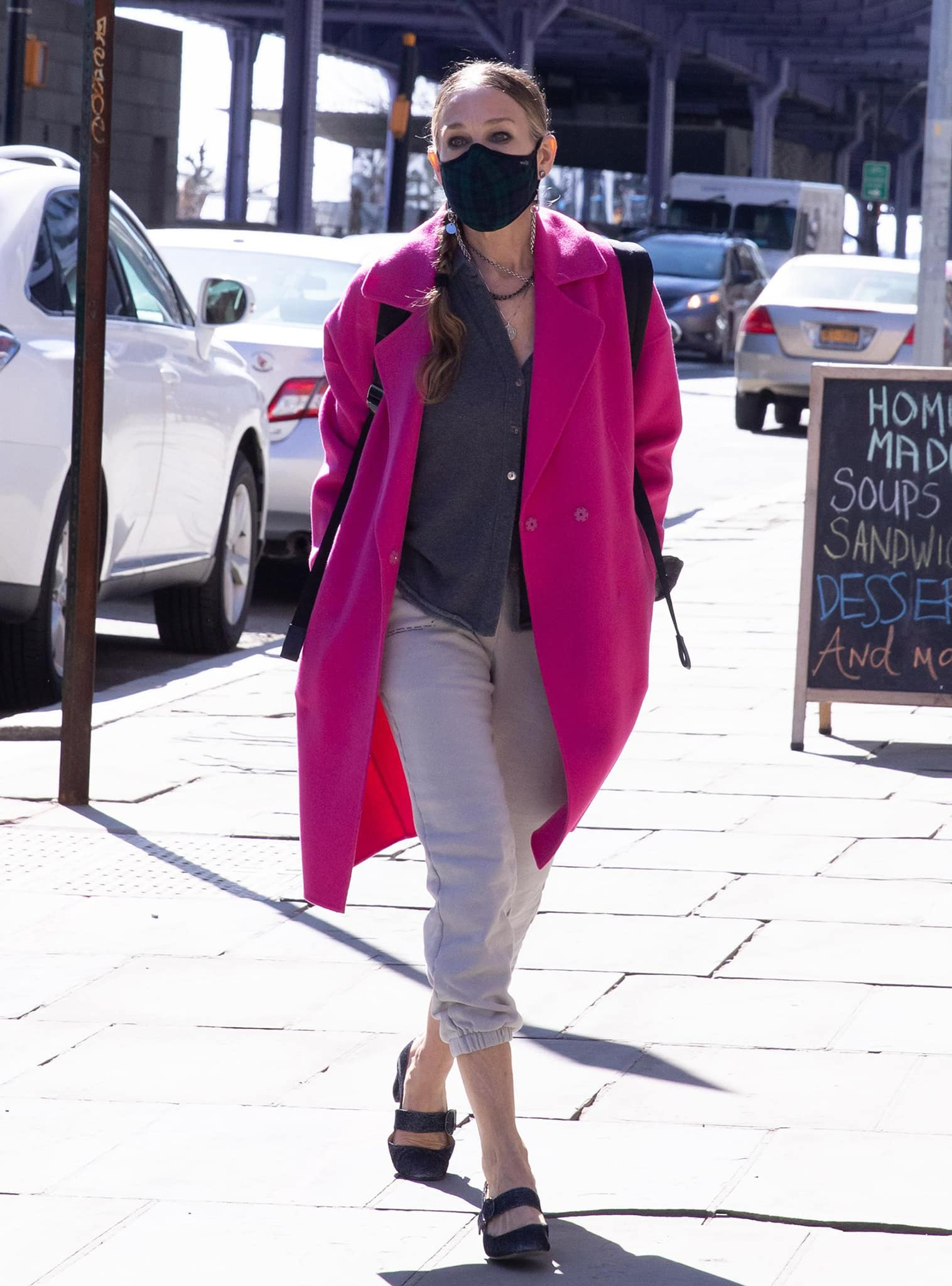 Sarah Jessica Parker visits her Downtown, New York store in Pangaia track pants and a pink Gerard Darel coat