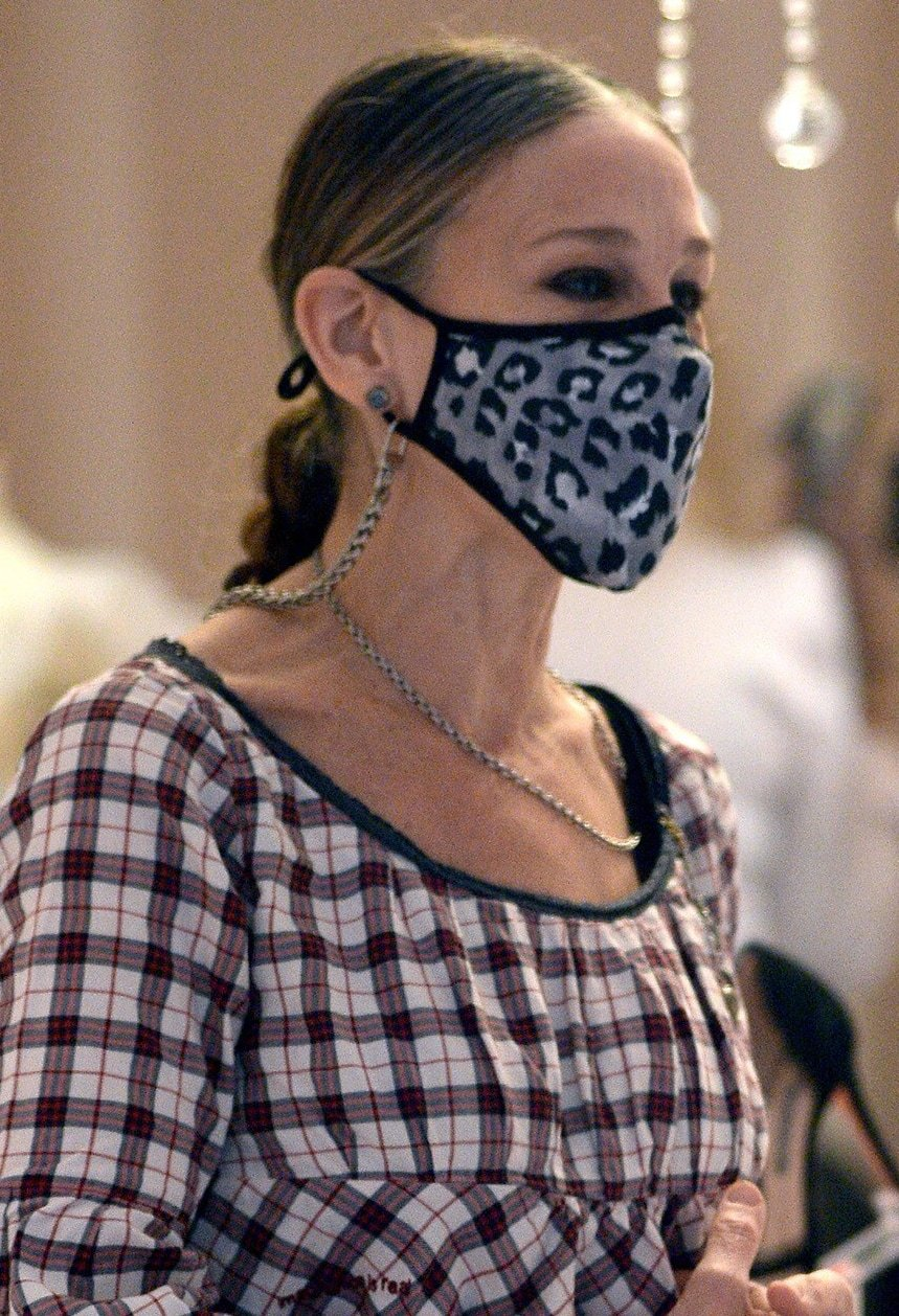 Sarah Jessica Parker styles her hair in a braided ponytail and wears a leopard-print face mask