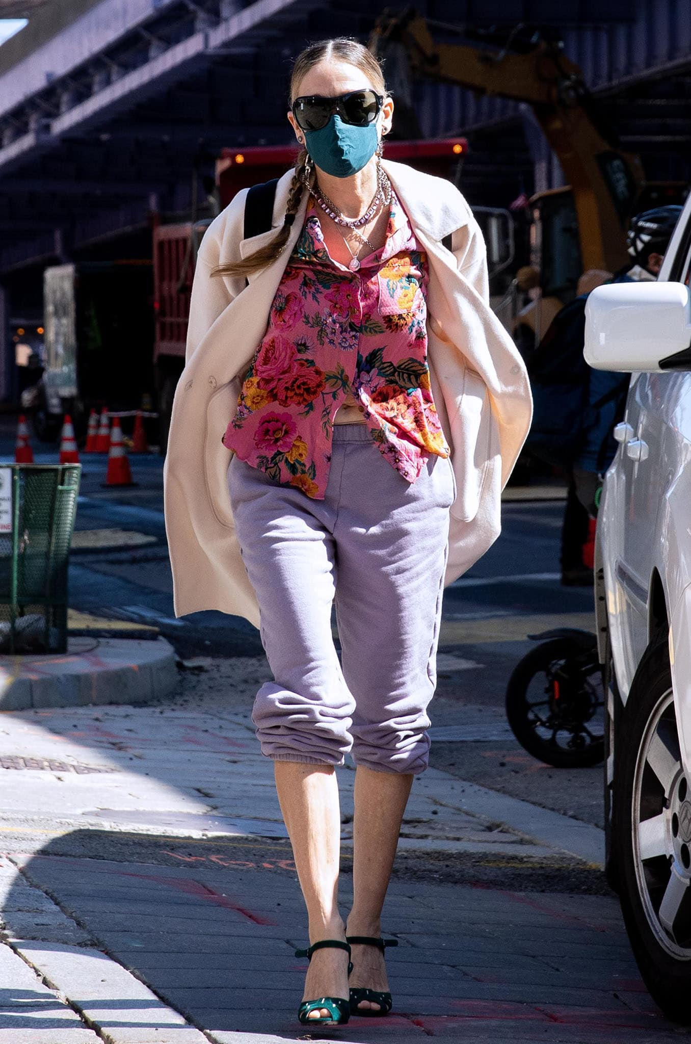 Sarah Jessica Parker teams her purple sweatpants with a floral shirt and a cream coat