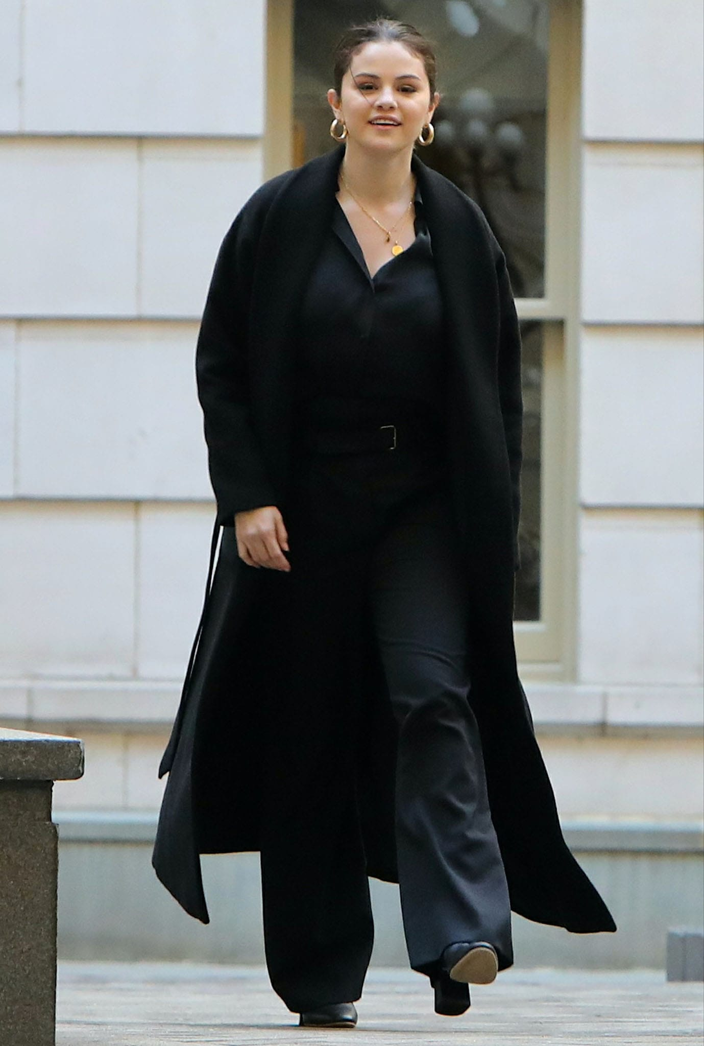 Selena Gomez wears a black coat over a black blouse tucked into a pair of high-waisted trousers