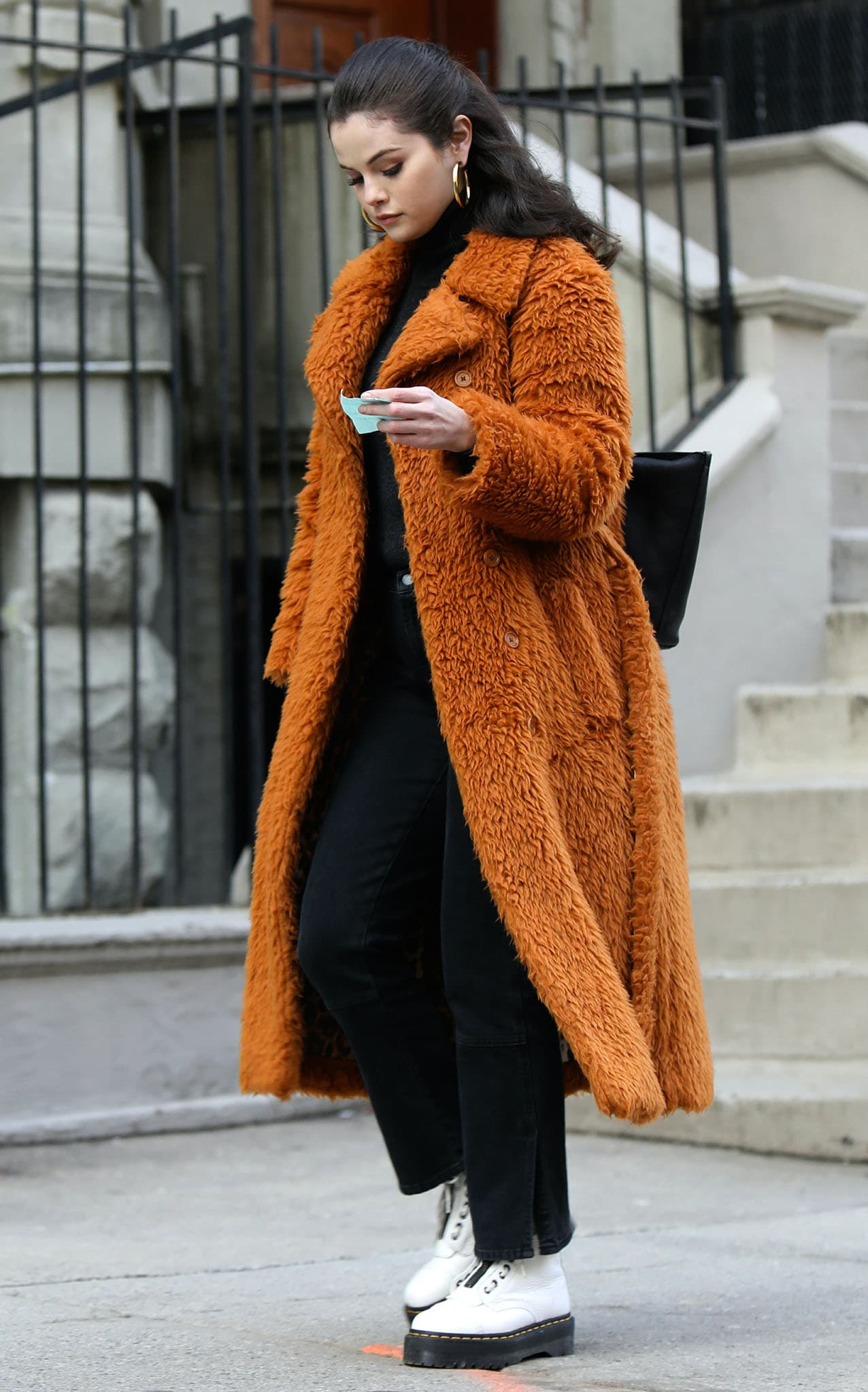 Selena Gomez wearing a brown teddy faux fur coat with a black turtleneck sweater
