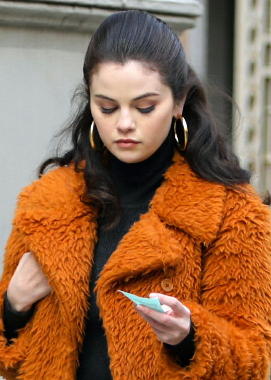 Selena Gomez ties her hair in a half-up style and accessorizes with gold hoop earrings