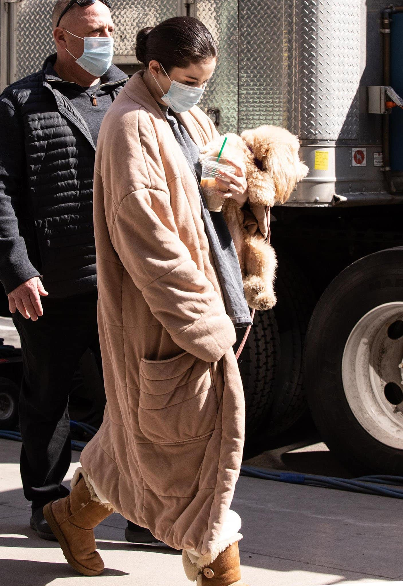 Selena Gomez looks cozy in Free People duvet coat and Ugg boots while carrying her fluffy dog, Daisy, on the set