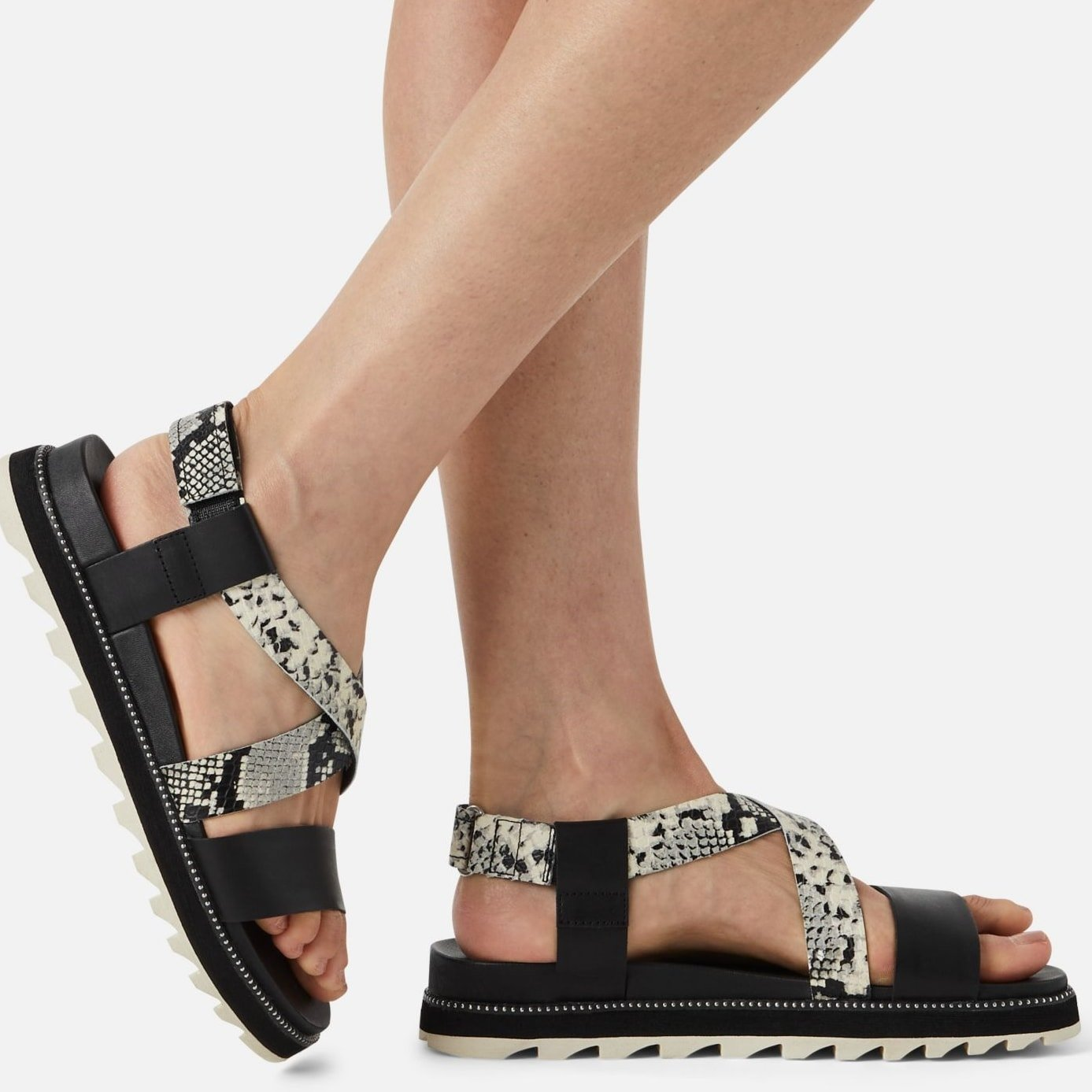 Monochrome straps cross atop a breezy sandal grounded by a sporty lugged sole that helps ensure sure-footed steps on all surfaces