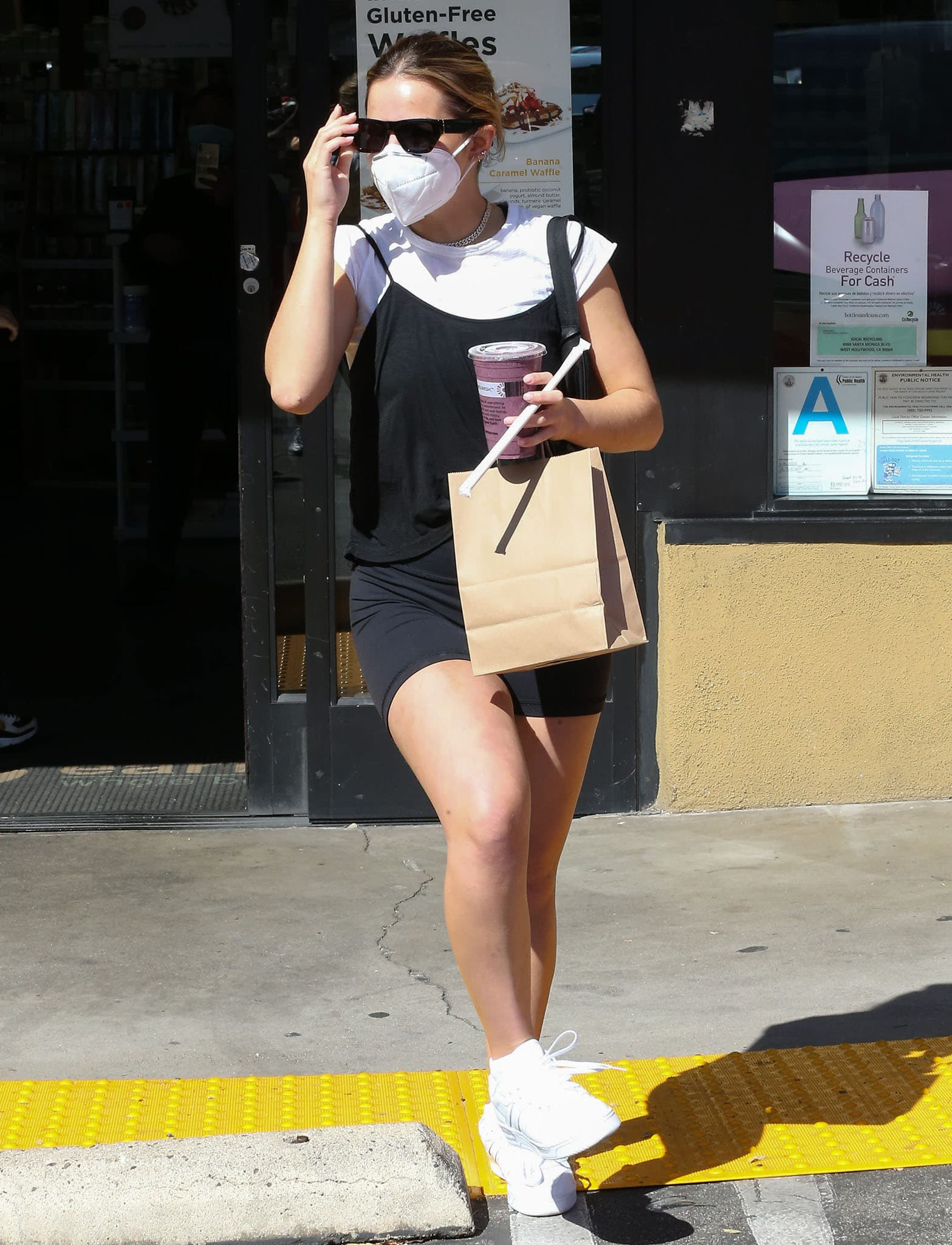 Addison Rae shows off her legs in biker shorts paired with a white tee and black camisole