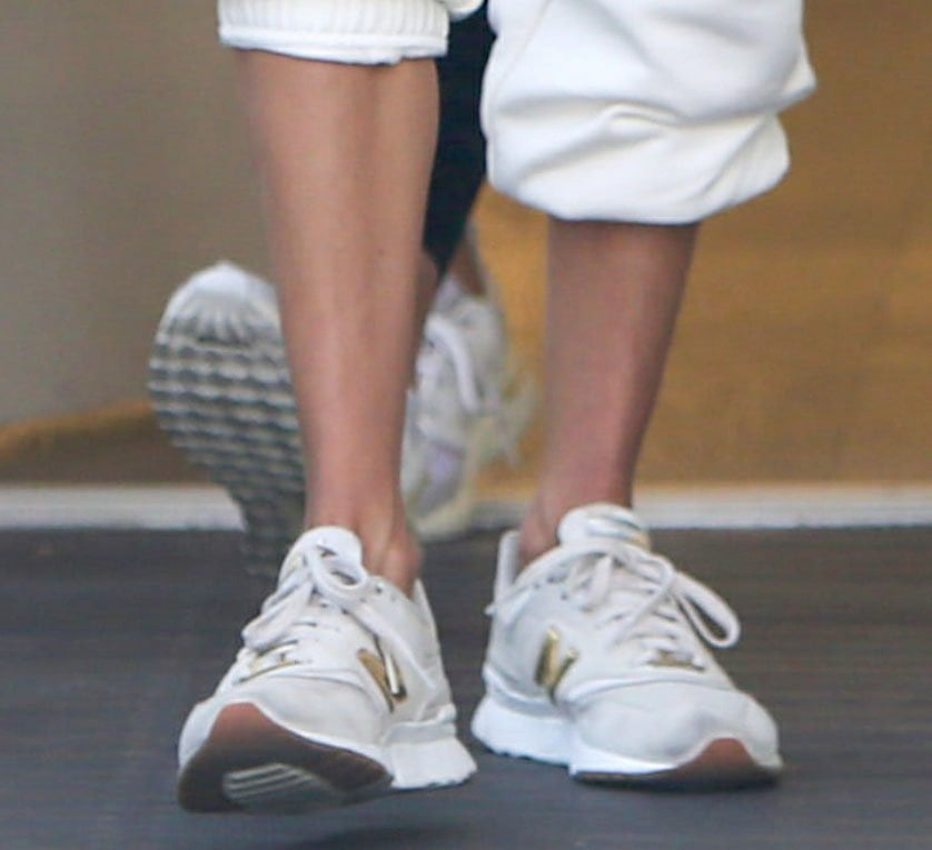 Alessandra Ambrosio completes an all-white sporty look with gray and gold New Balance 997H sneakers